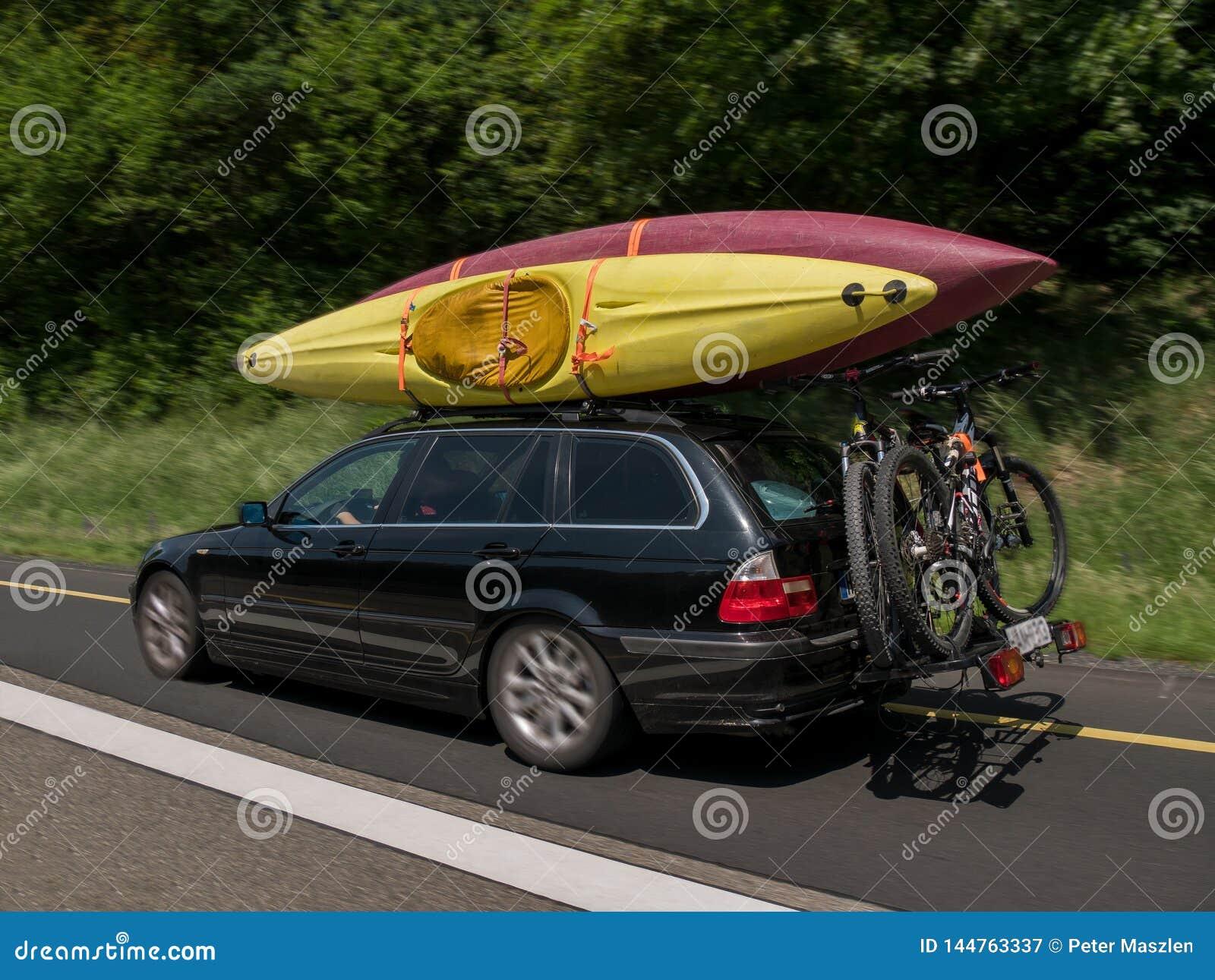Автомобиль с каяками на верхней части и велосипедами на задней части и