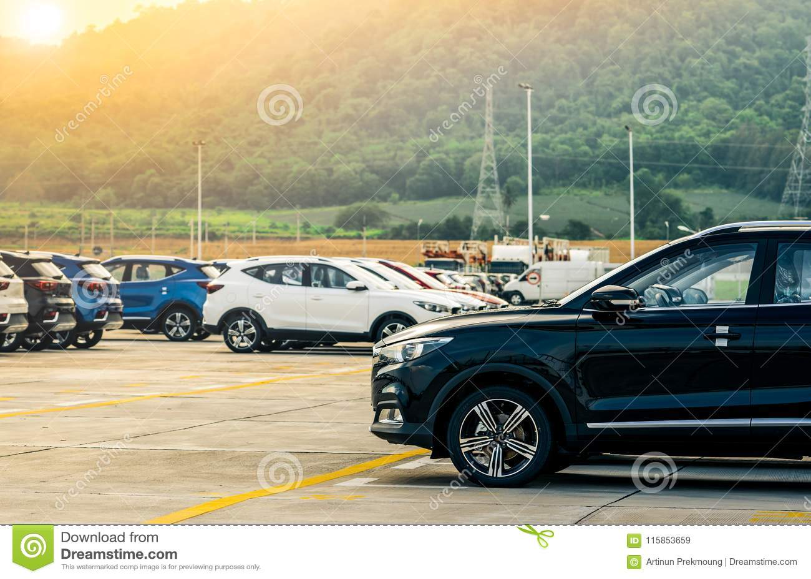 Автомобиль черноты, белых и голубых новый припарковал на конкретной стояночной площадке на фабрике около горы Концепция автосалон