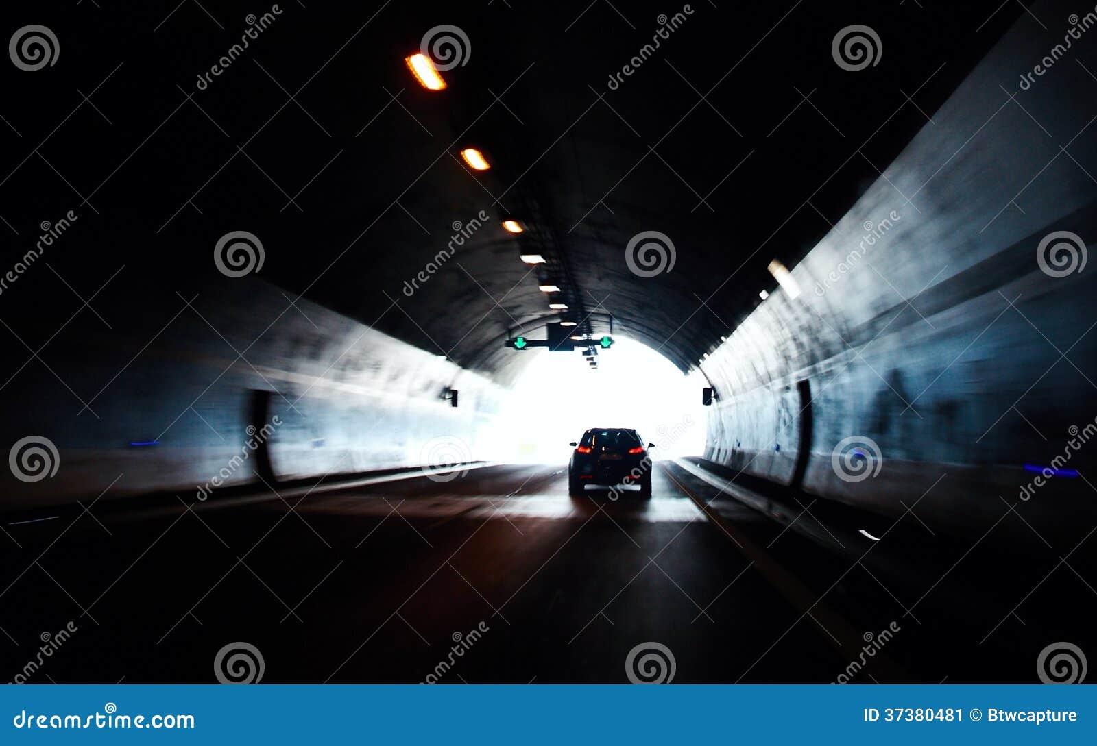 Автомобиль двигая вне от тоннеля дороги