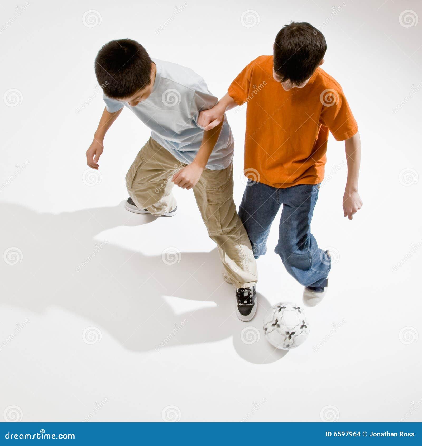агрессивныйый футбол мальчика шарика принимает к пробовать