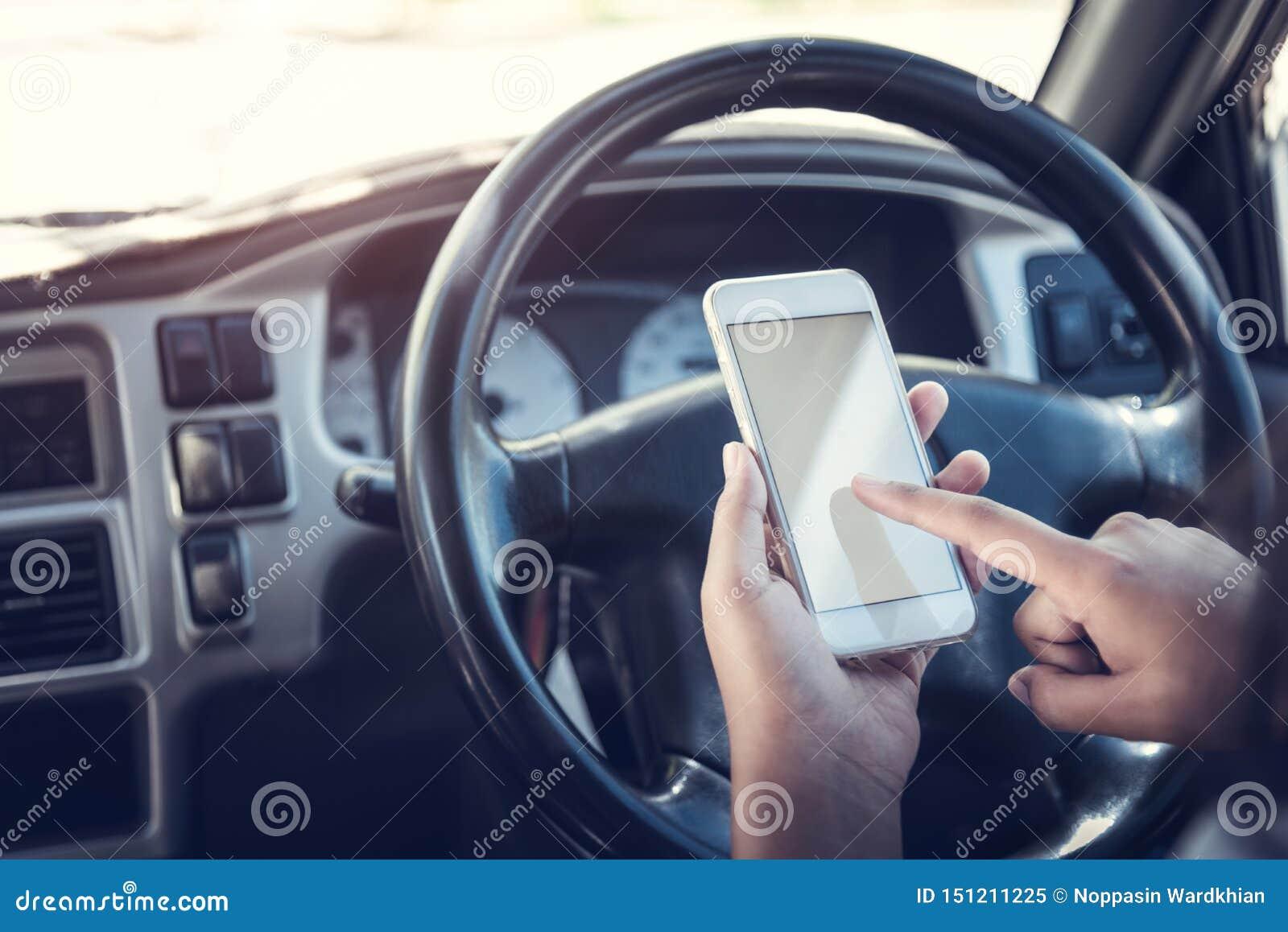 Азиатская беседа женщины чернью вызывая отправку SMS и смотря на мобильном телефоне пока сидящ в ее автомобиле, вождении под влия