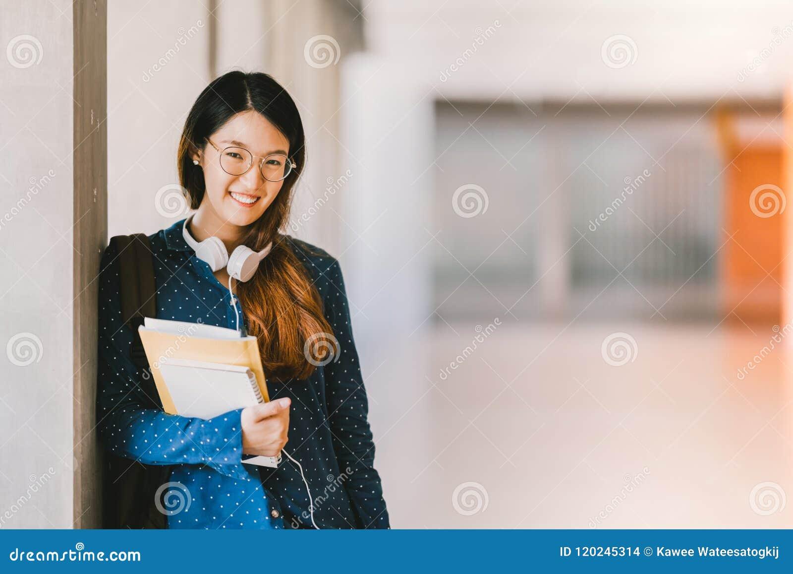 Азиатская девушка средней школы или eyeglasses студента колледжа нося, усмехаясь в университетском кампусе с космосом экземпляра