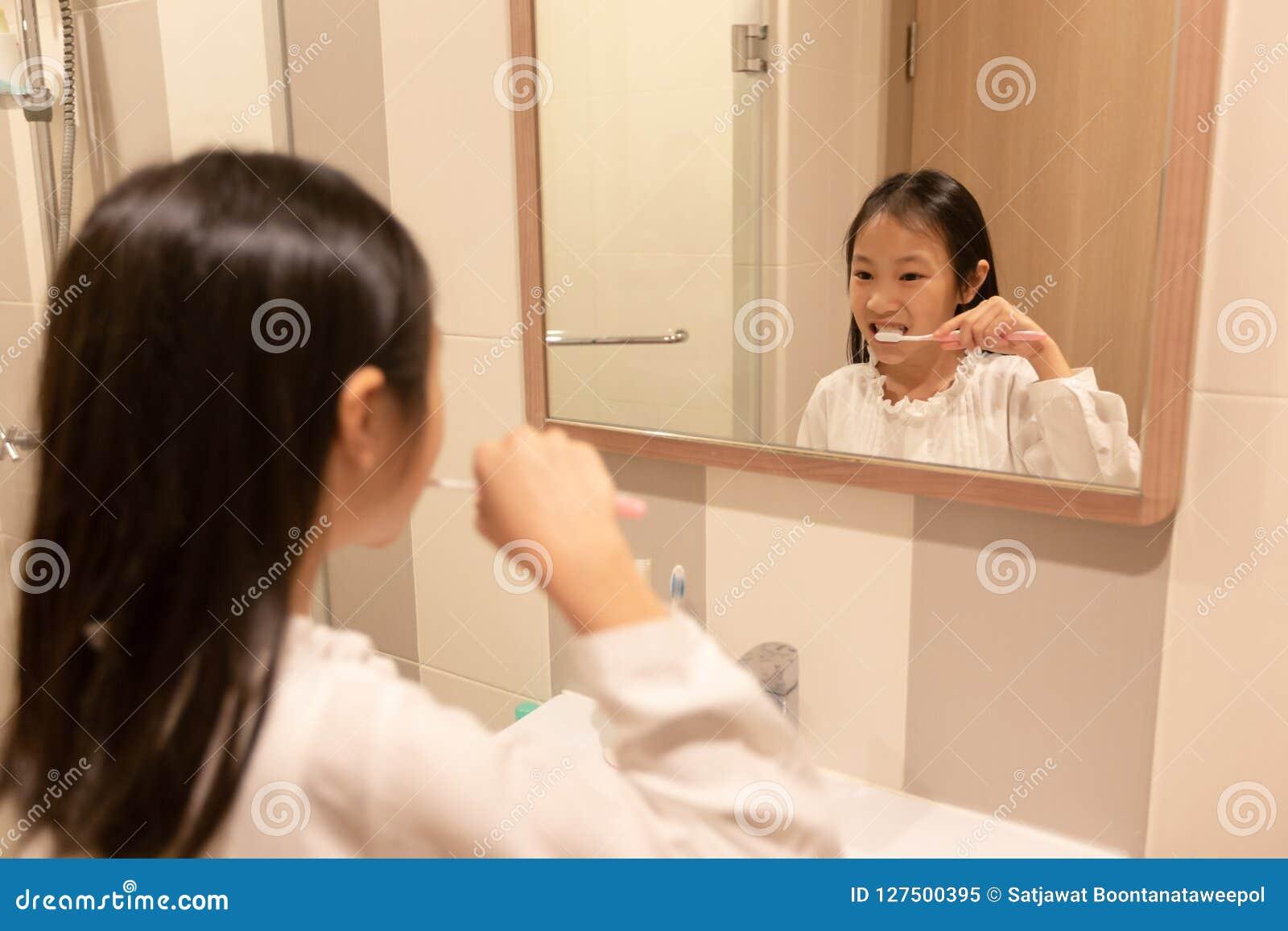 Азиатская девушка чистит ее зубы щеткой и усмехается пока смотрящ в th
