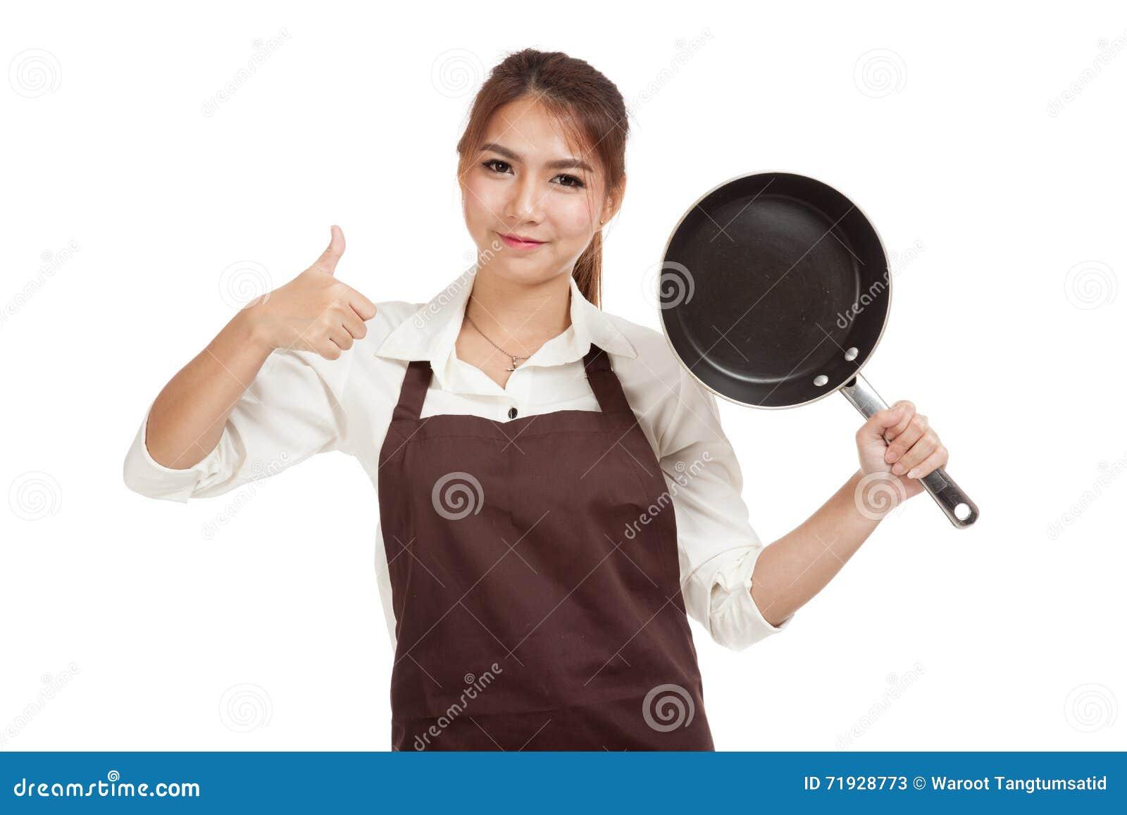Азиатская девушка варя большие пальцы руки вверх с сковородой