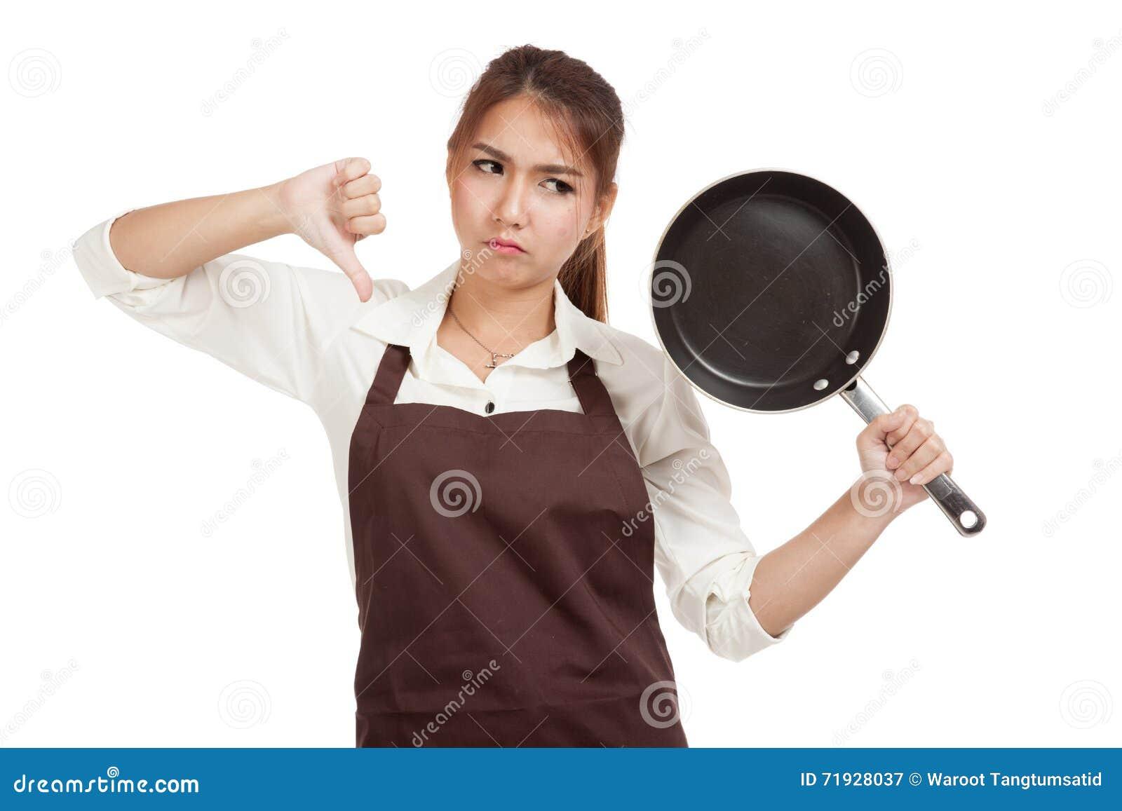 Азиатская девушка варя большие пальцы руки вниз с сковородой