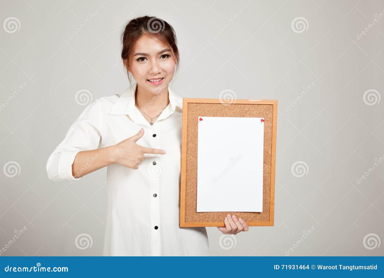 Азиатская девушка с штырем чистого листа бумаги на пробковой доске