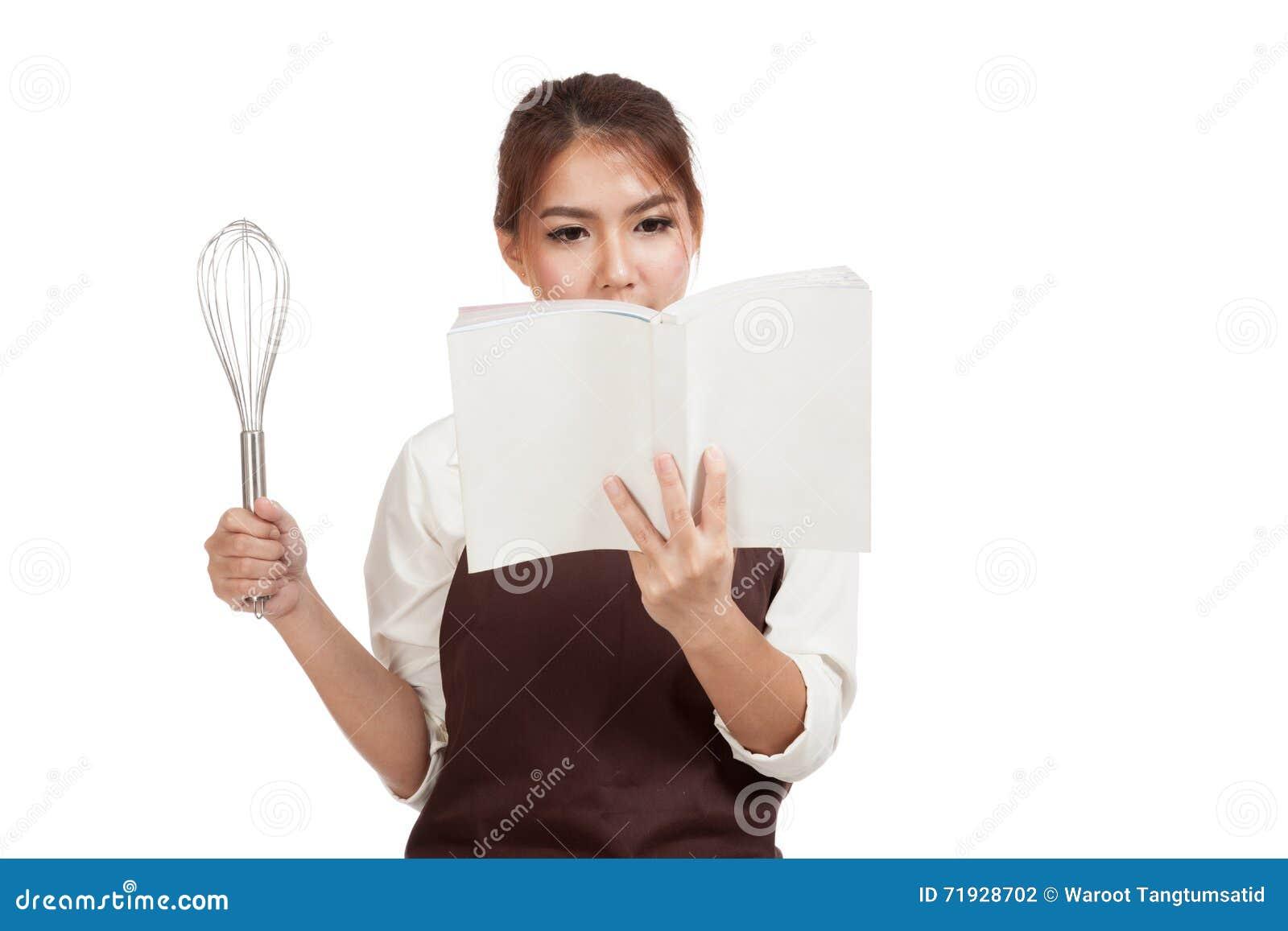 Азиатская девушка хлебопека с юркнет и варит книга