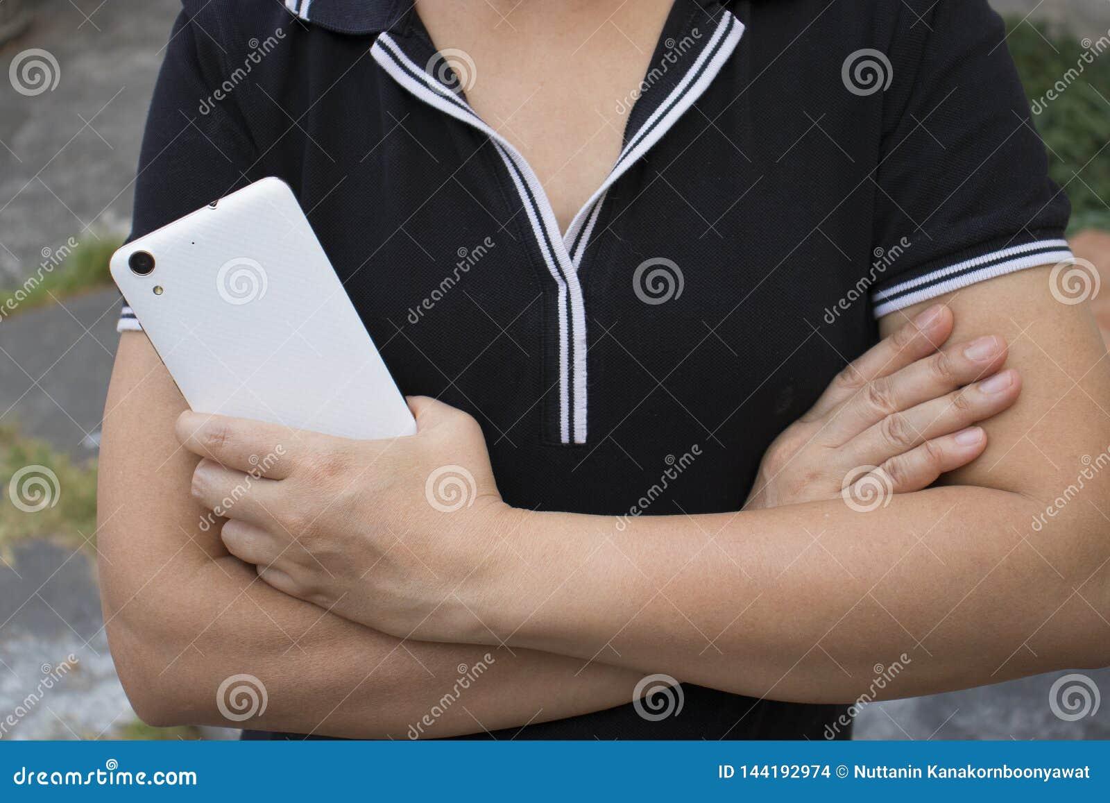 Азиатская женщина держа и используя умную сторону шоу телефона назад