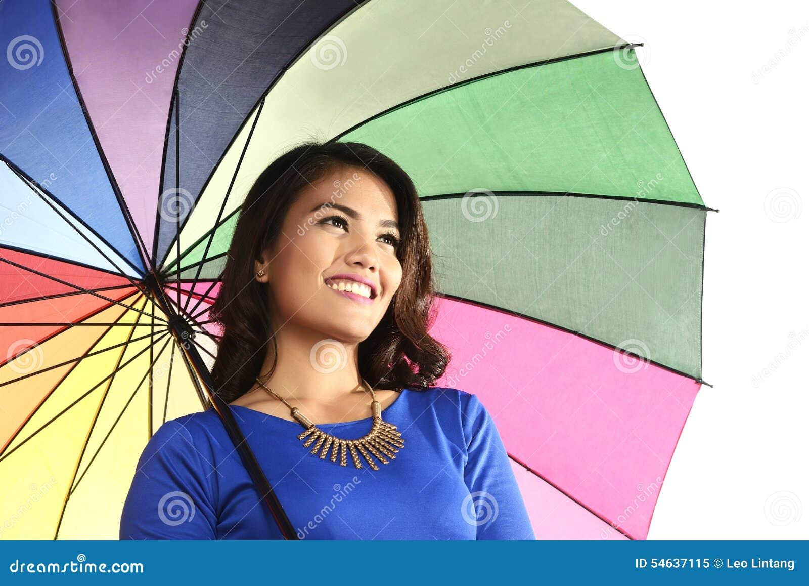 Азиатская женщина держа усмехаться зонтика