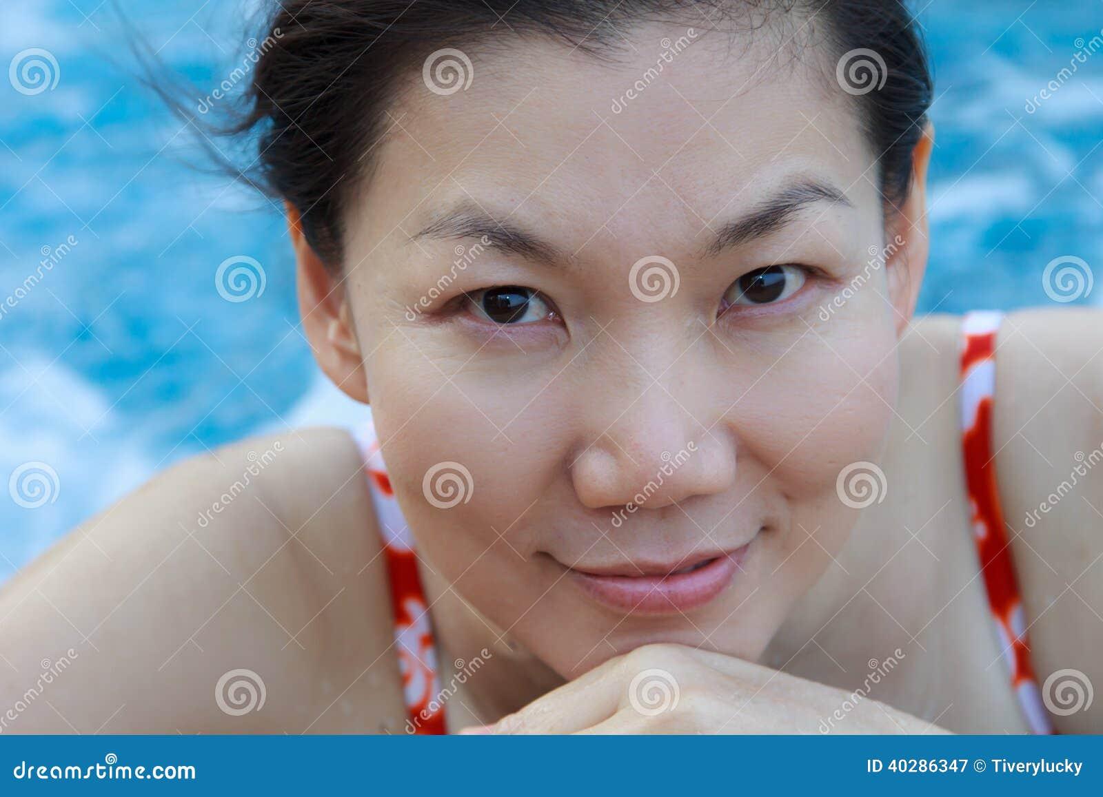 Азиатская женщина наслаждаясь и ослабляя в бассейне.