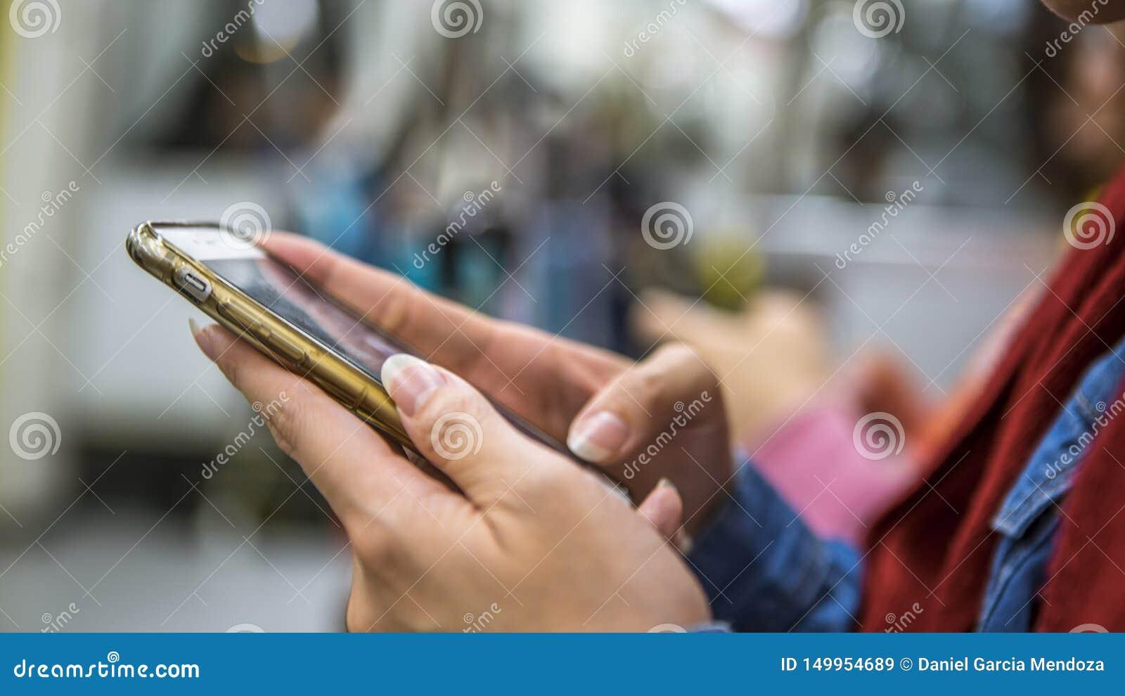 Азиатская женщина сидит вниз в смартфоне метро и владений Пассажир используя телефон