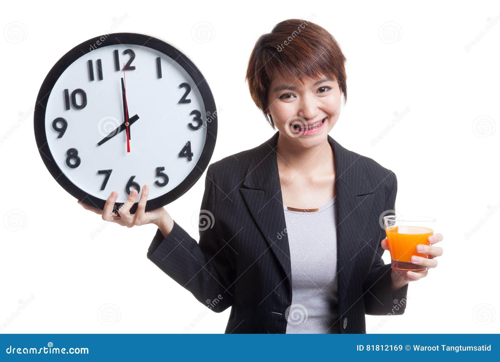 Азиатская женщина с апельсиновым соком питья часов