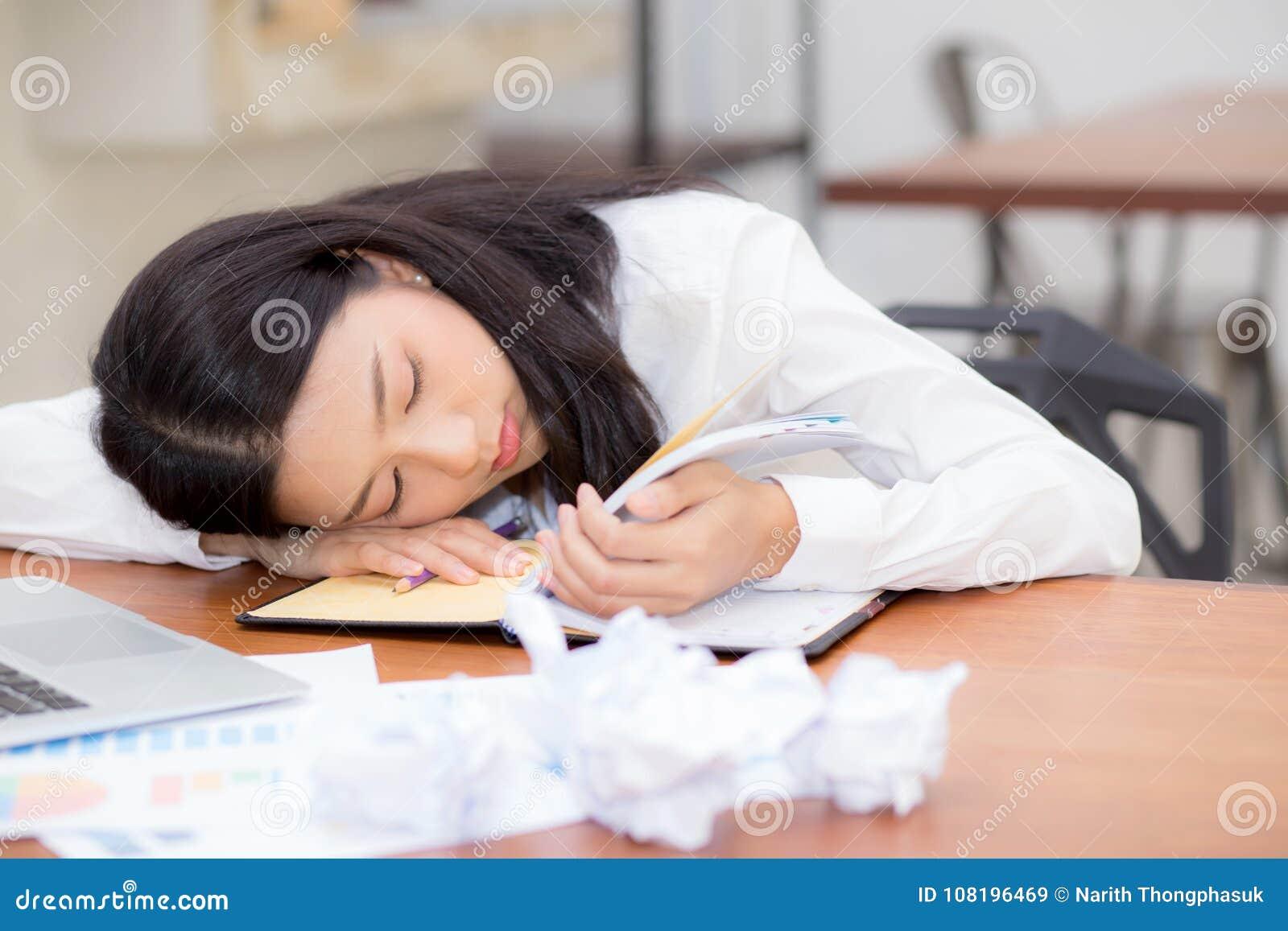 Азиатская женщина с утомленный перегружать и сон, девушка имеют отдыхать пока примечание сочинительства работы
