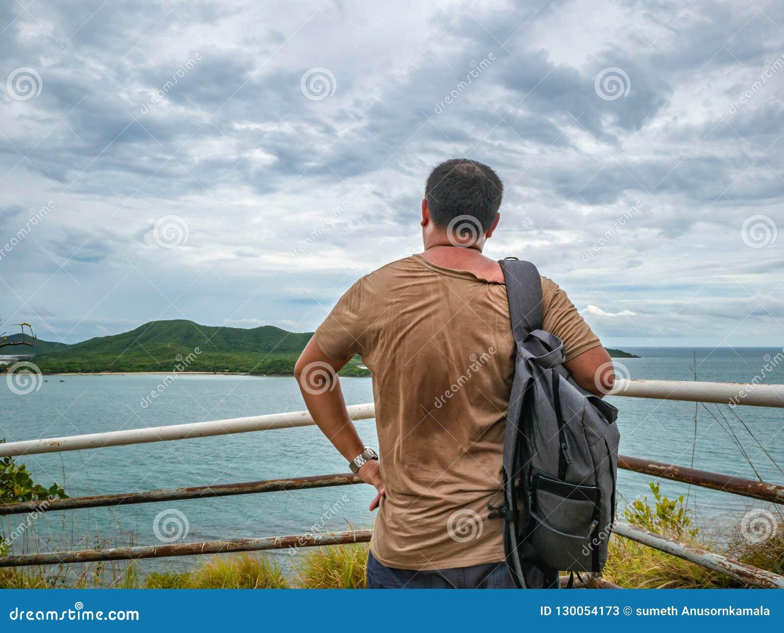 Азиатская жирная стойка путешественника на точке зрения с тропическим идилличным океаном и белым небом облака в отпуске
