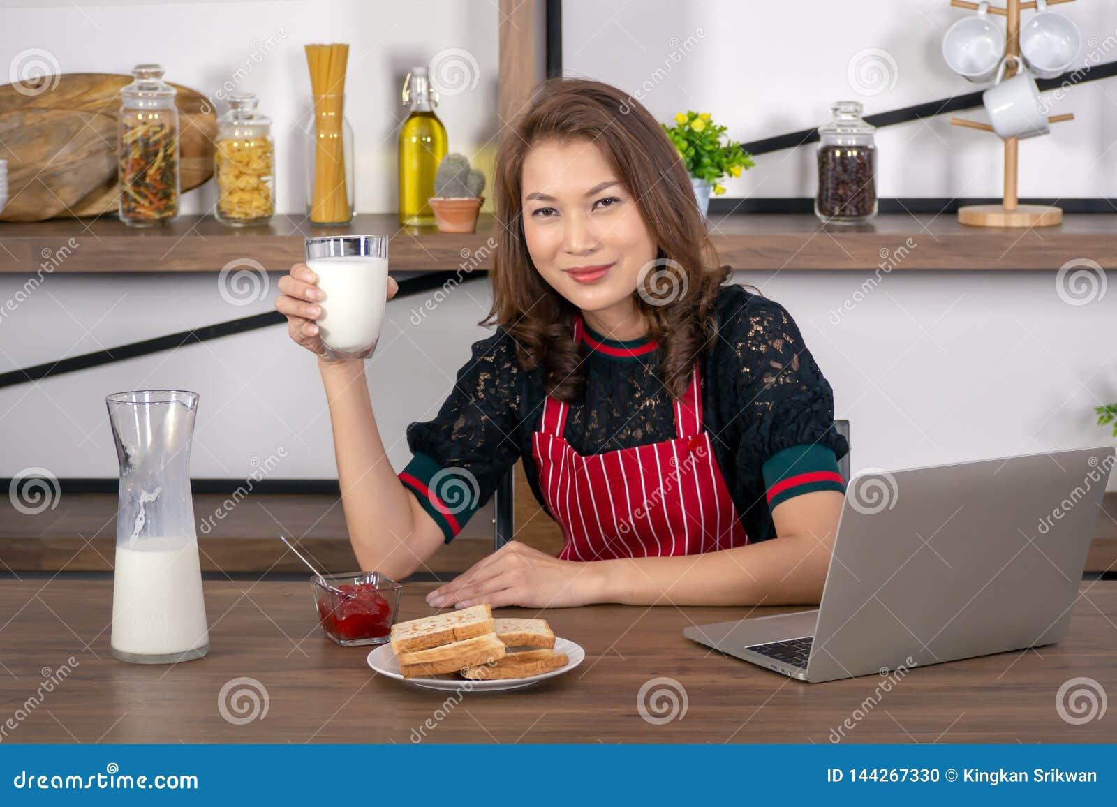 Азиатская красивая женщина держа стекло молока