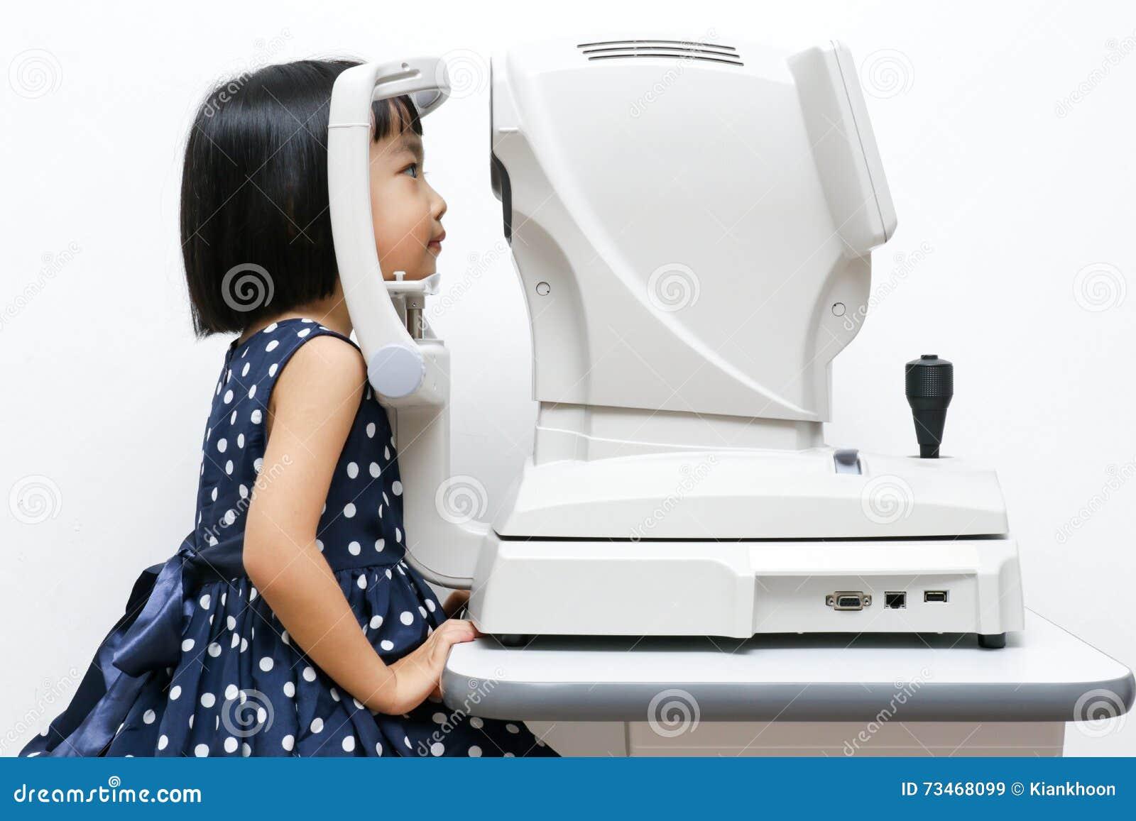 Азиатская маленькая китайская девушка делая рассмотрение глаз через автоматический re