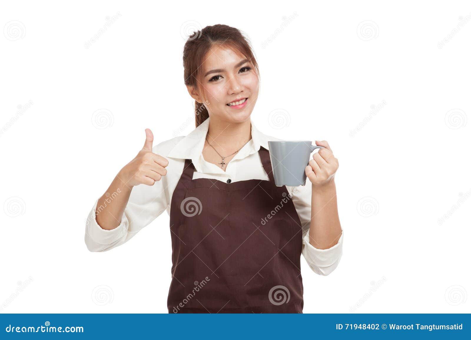 Азиатская официантка в больших пальцах руки рисбермы вверх с чашкой кофе