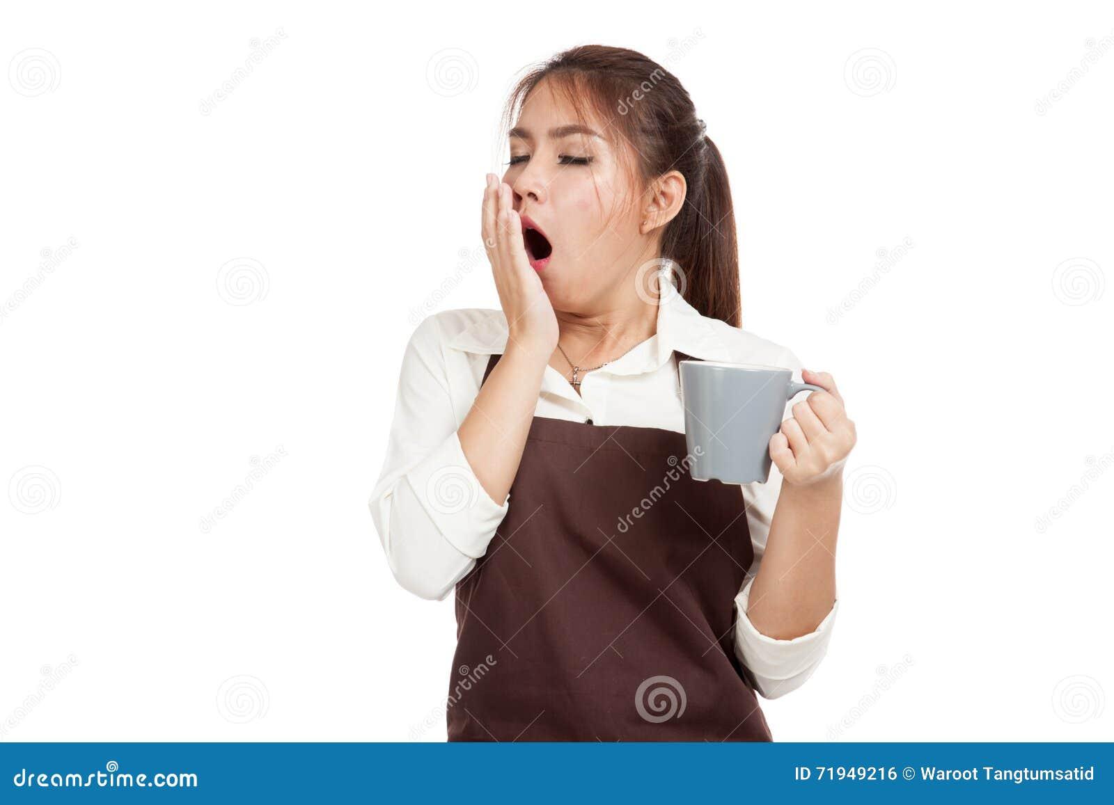Азиатская официантка в зевке рисбермы с чашкой кофе