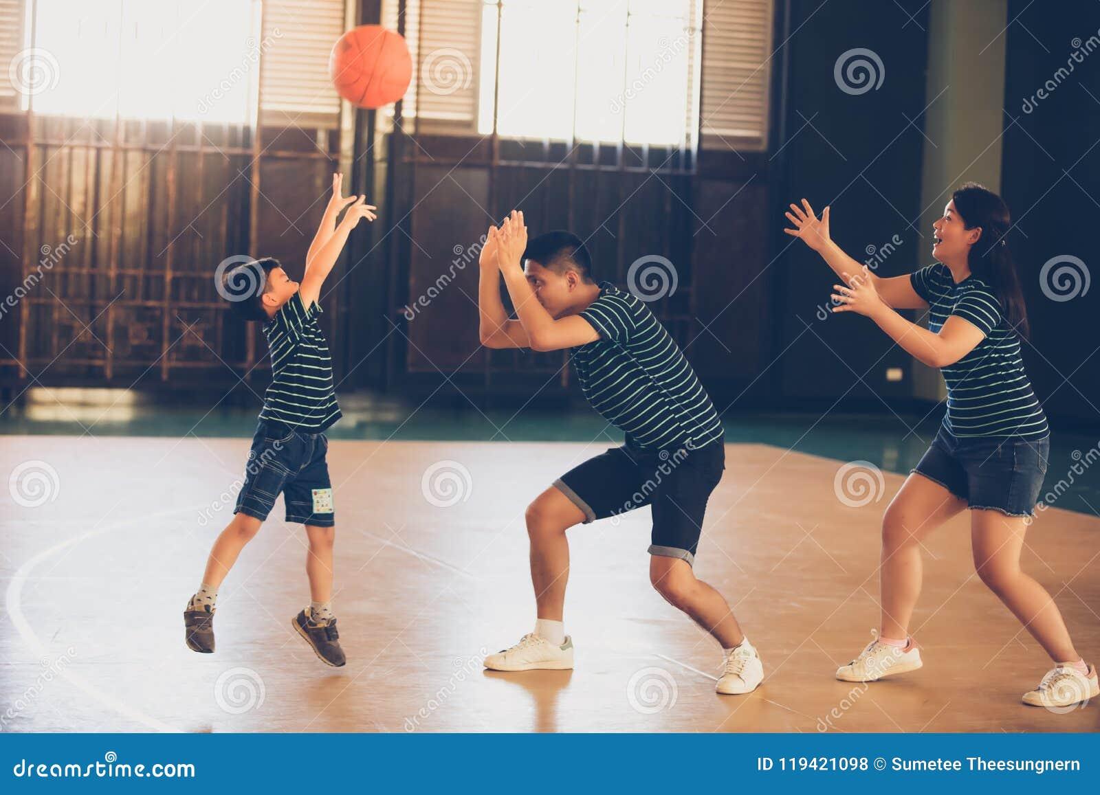 Азиатская семья играя баскетбол совместно Счастливая трата семьи