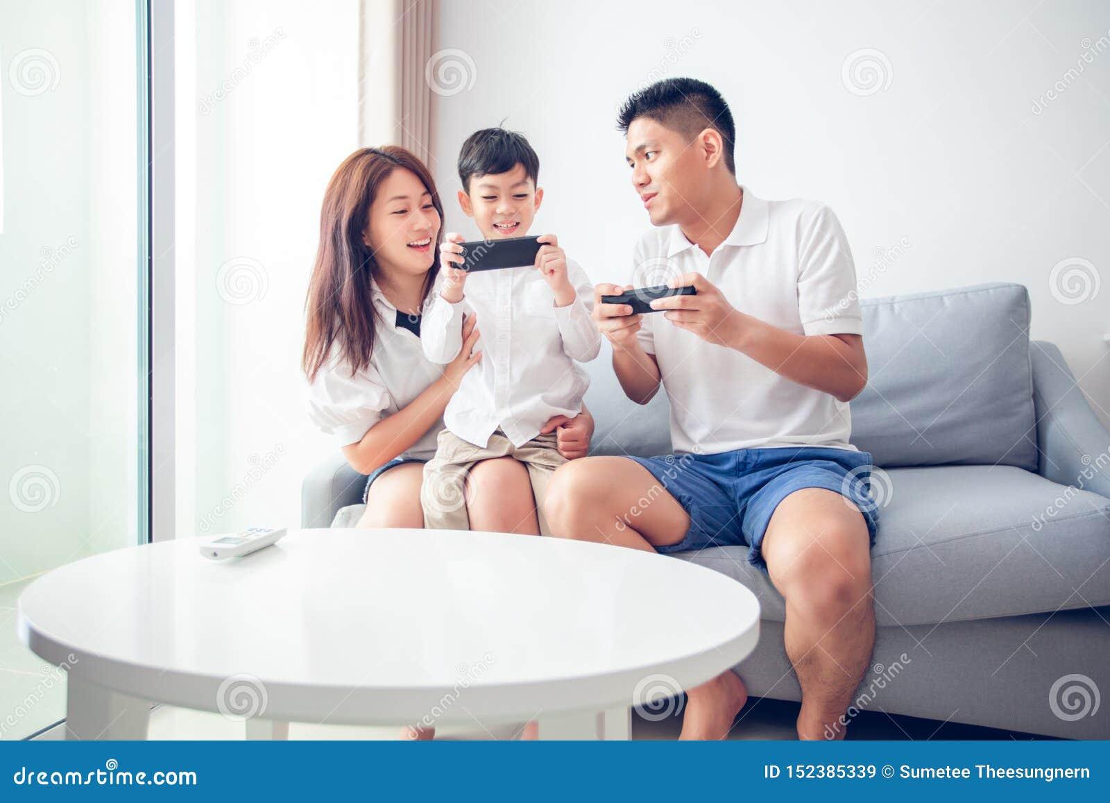 Азиатская семья имея потеху играя игры консоли компьютера совместно, отец и сын имеют регуляторы телефонной трубки и мать