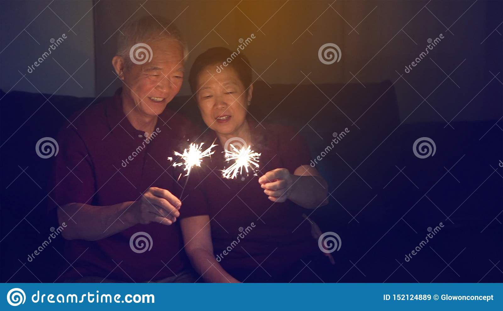 Азиатская старшая пара празднуя совместно дома сверкнает фейерверк s
