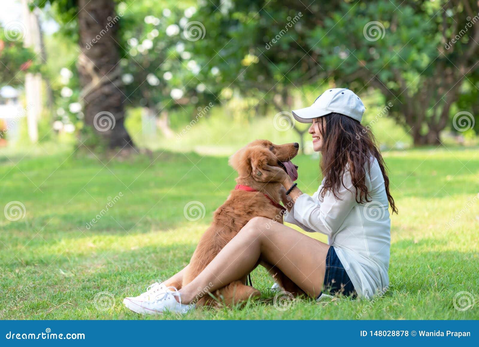 Азиатская smilling женщина образа жизни играя и счастливая с собакой приятельства золотого retriever в восходе солнца