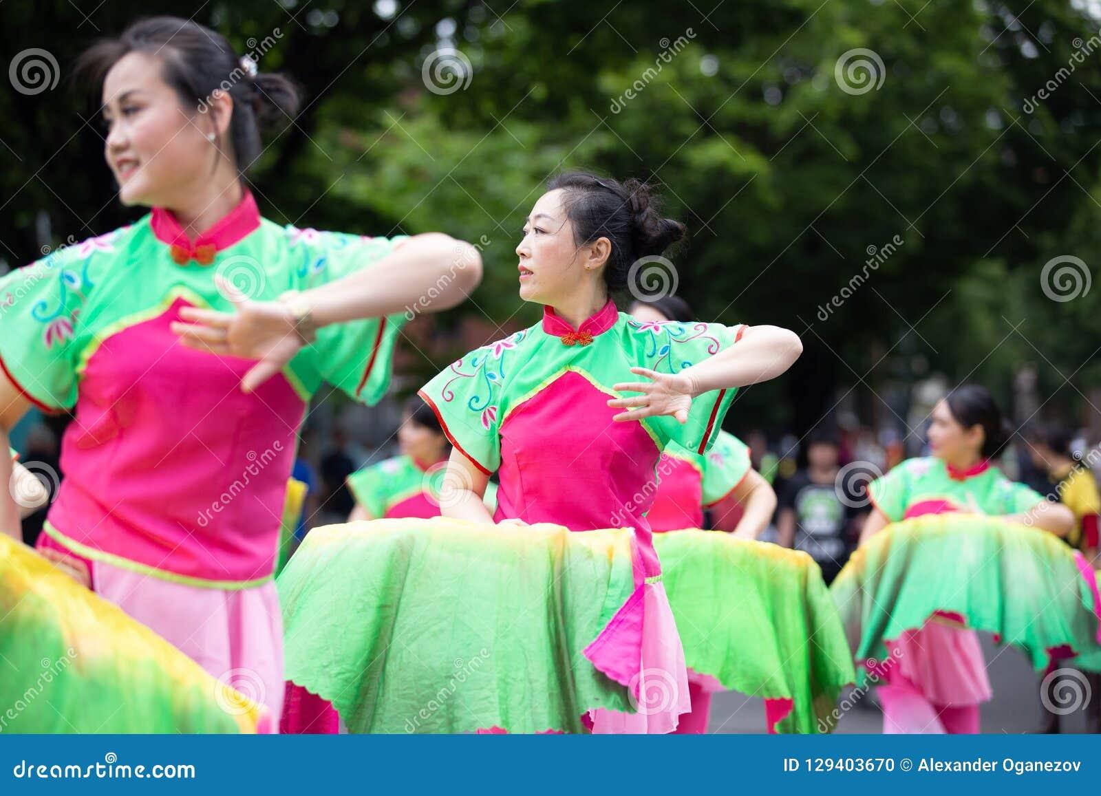 Азиатские дамы в традиционных танцах костюма на улице