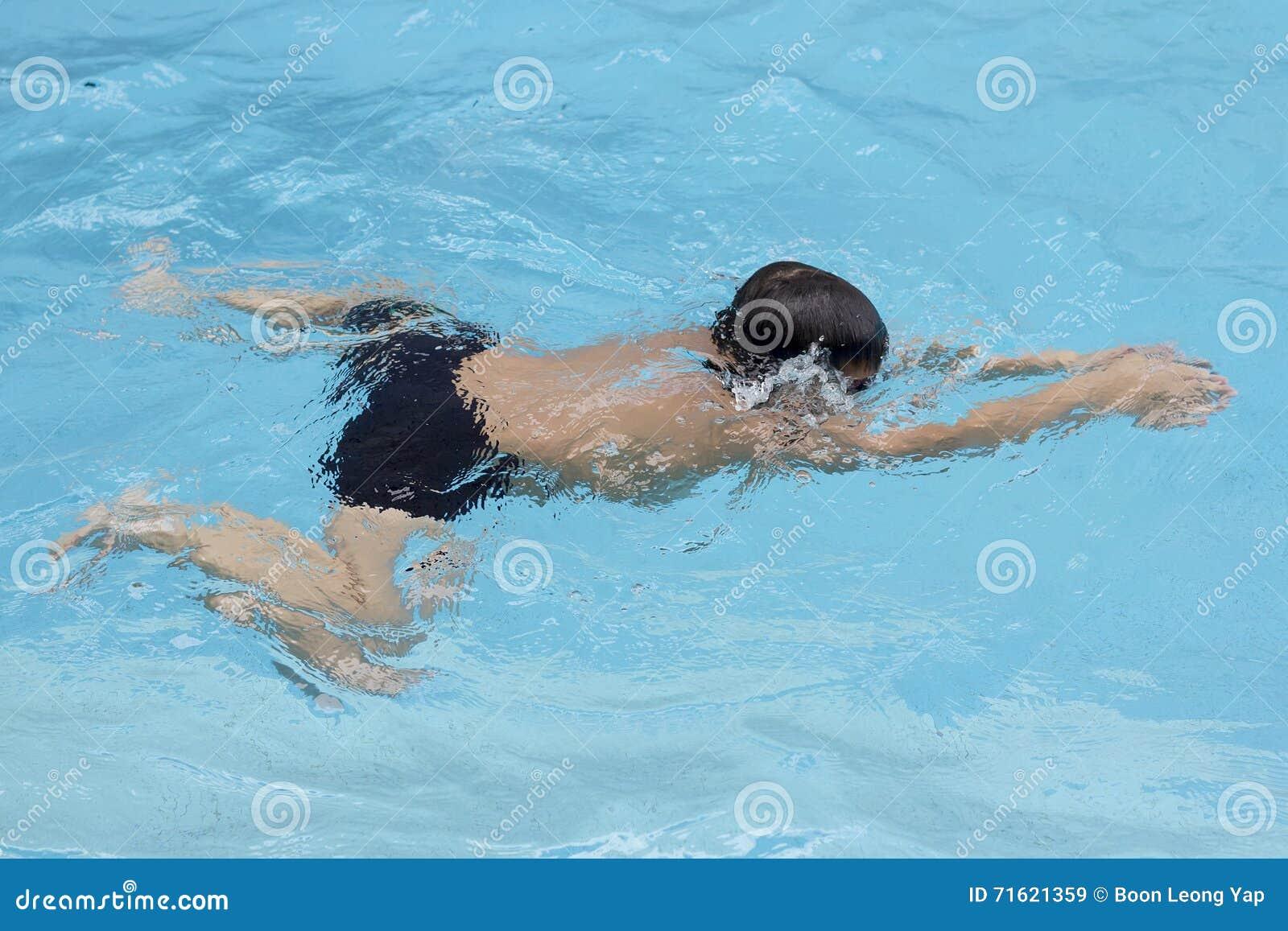 Азиатские заплывы хода груди мальчика в бассейне