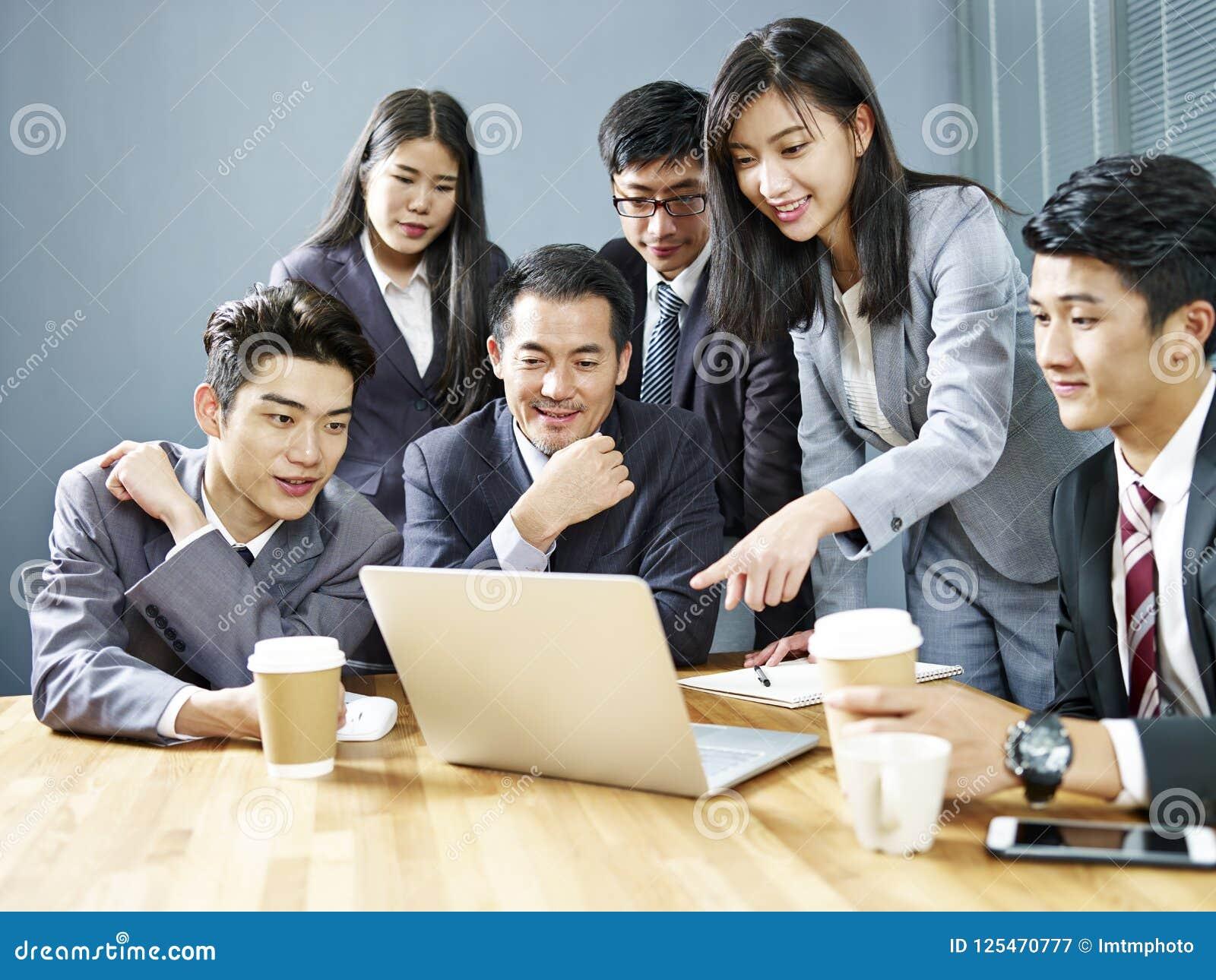 Азиатские корпоративные люди рассматривая результаты дела