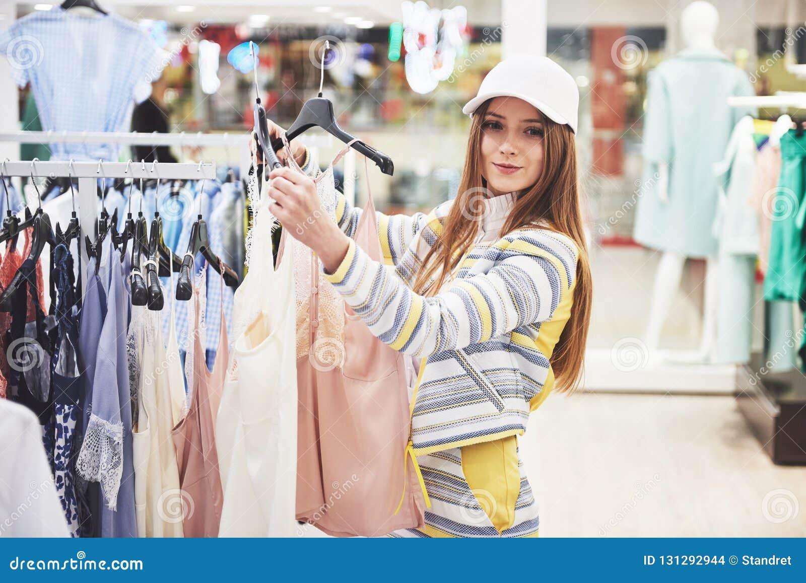 азиатские красивейшие кавказские одежды одевая женскую счастливую внутри помещения смотря женщину магазина модельной покупкы поку