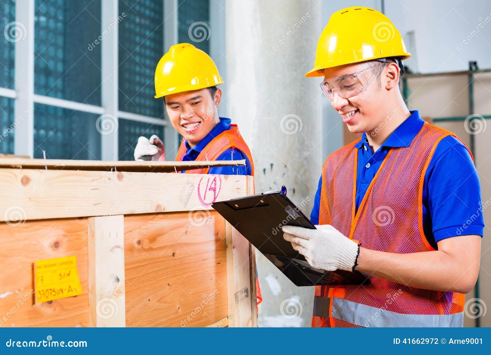 Азиатские рабочий-строители на месте раскрывают деревянную коробку