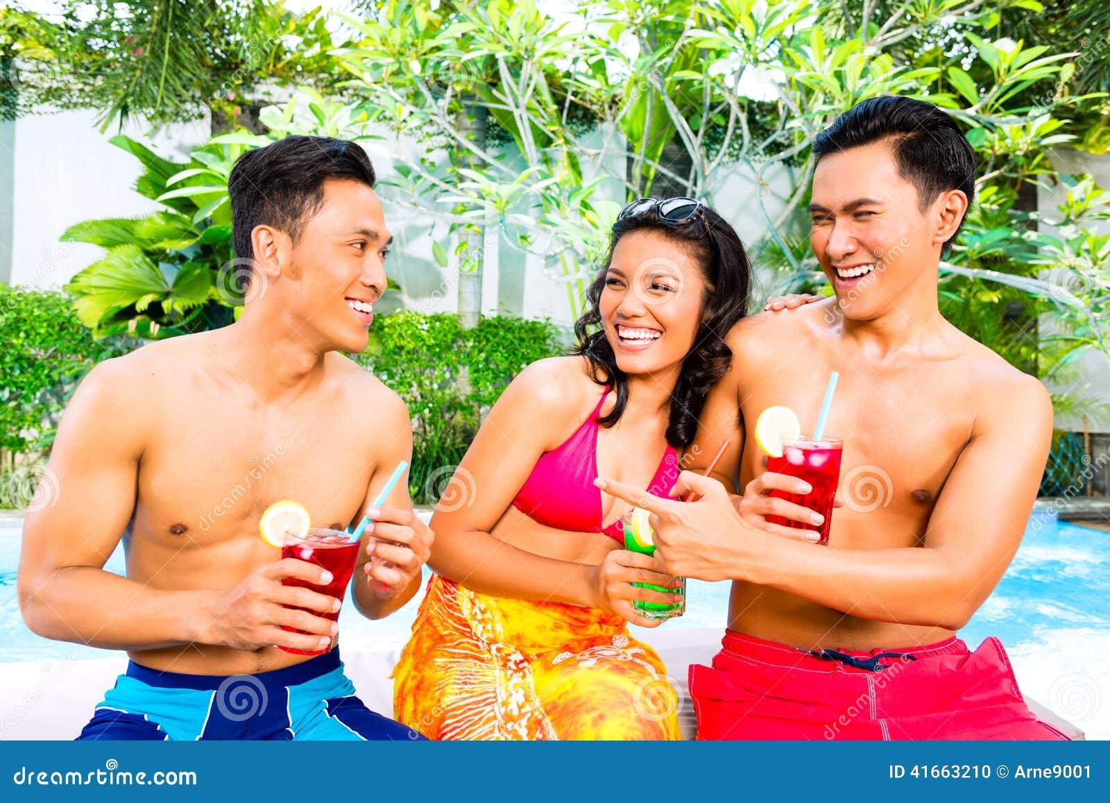 Азиатские друзья выпивая коктеили на бассейне