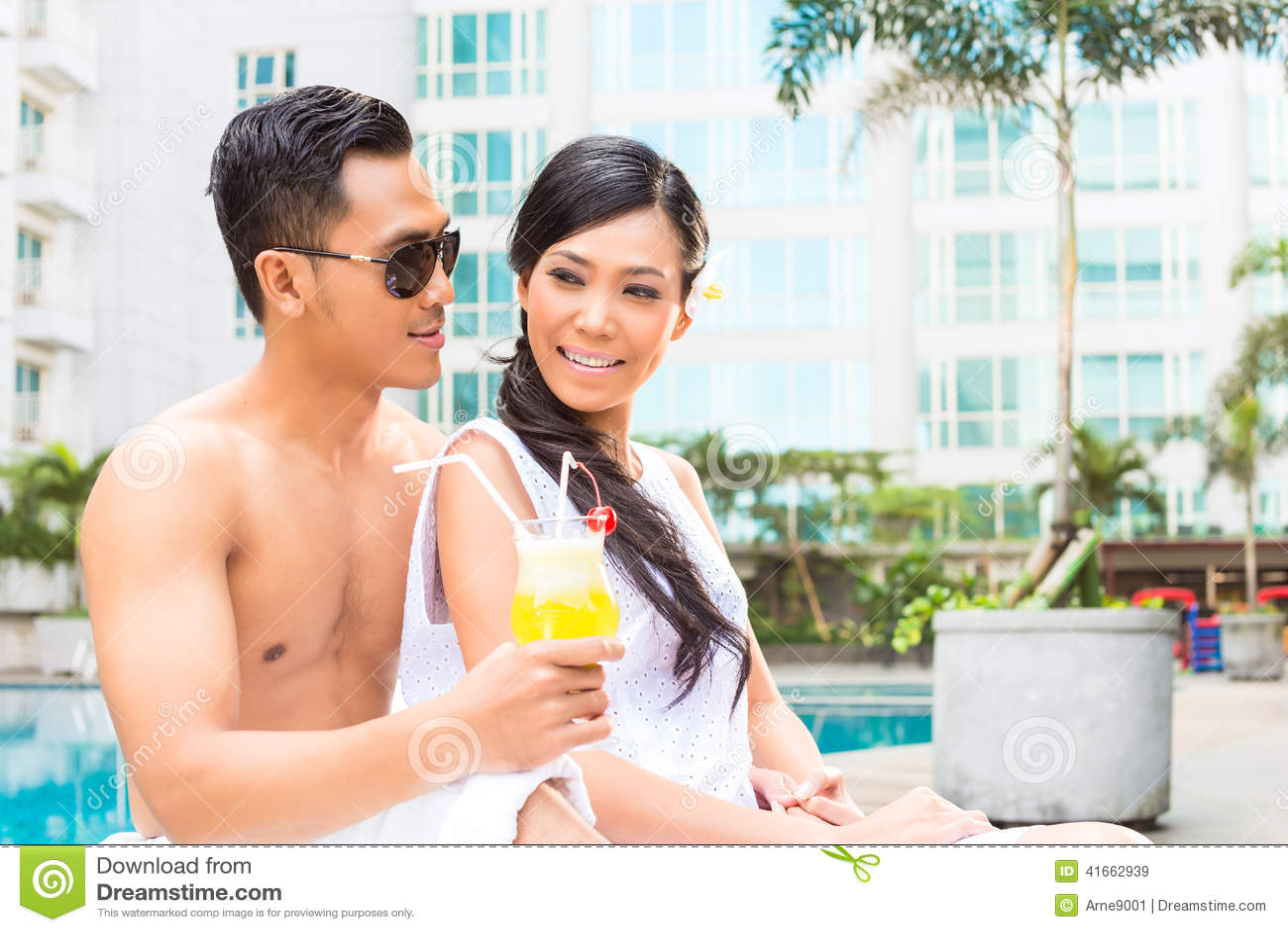 Азиатские друзья сидя бассейном гостиницы