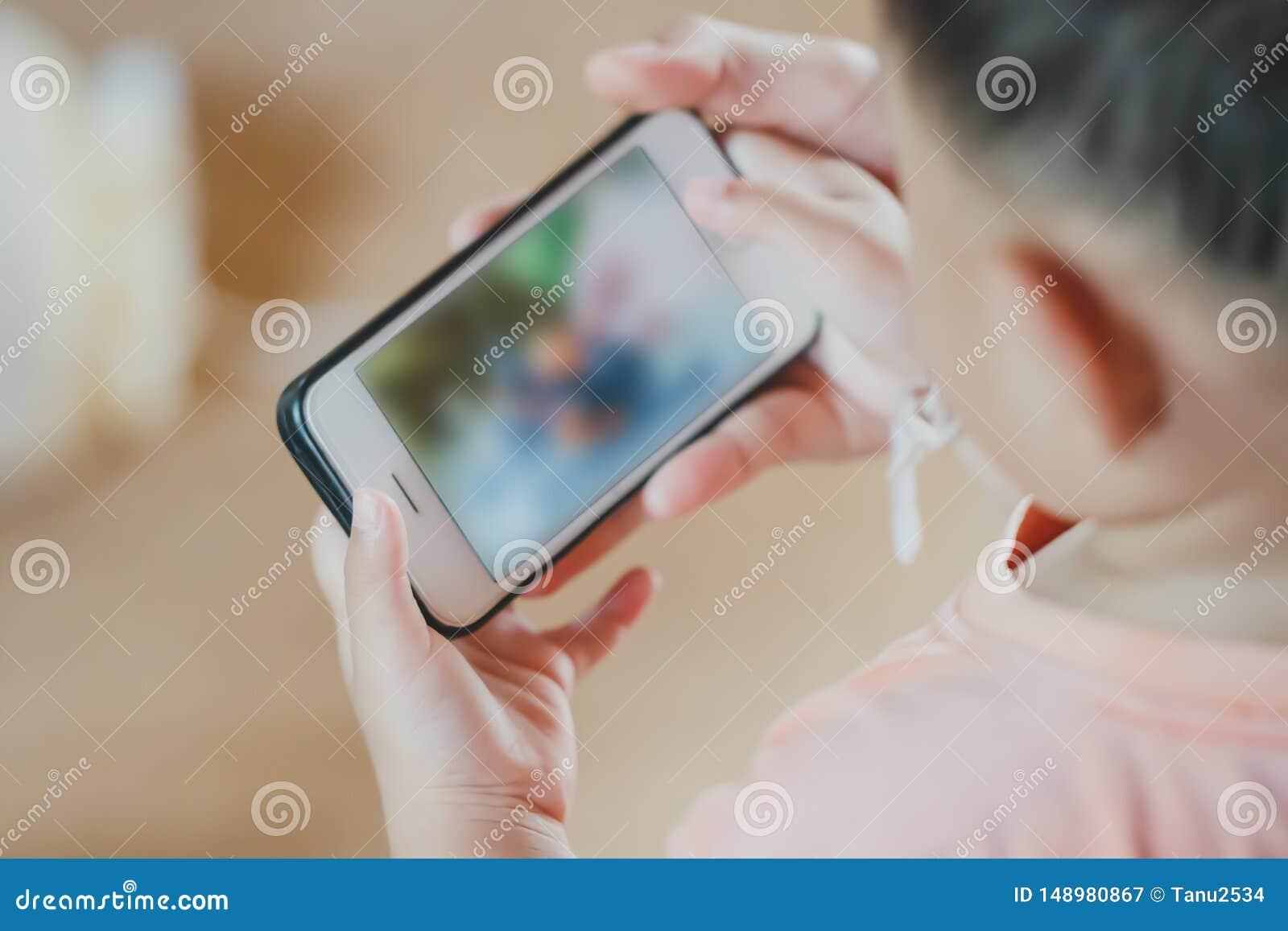 Азиатские удерживание мальчика ребенка и экран касания смартфона