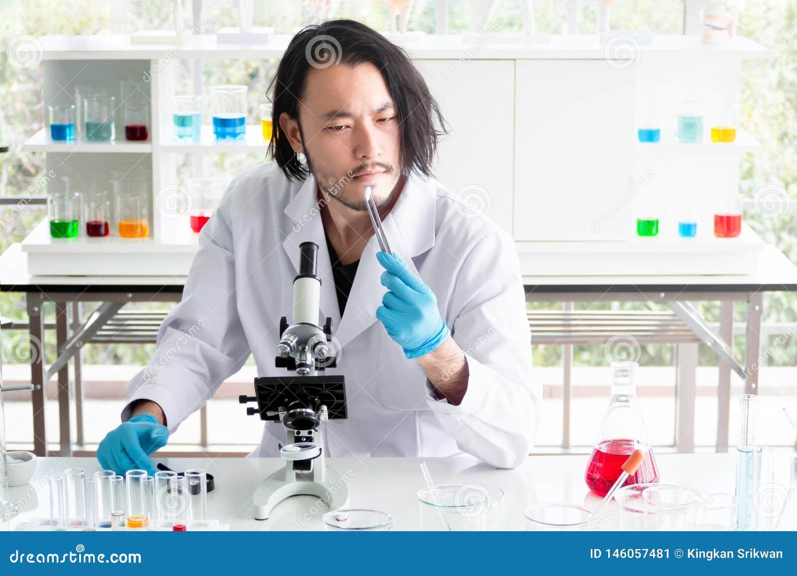 Азиатские ученый или химик смотря планшет в лаборатории, медицину молодого человека испытывая в медицинском эксперименте r
