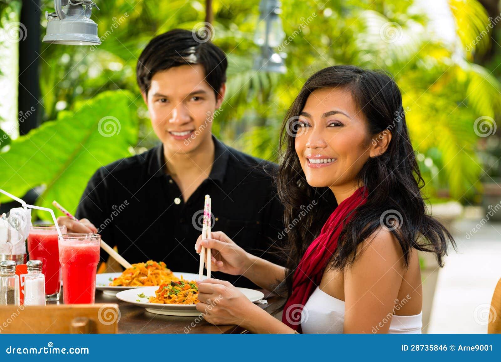 Азиатские человек и женщина в ресторане