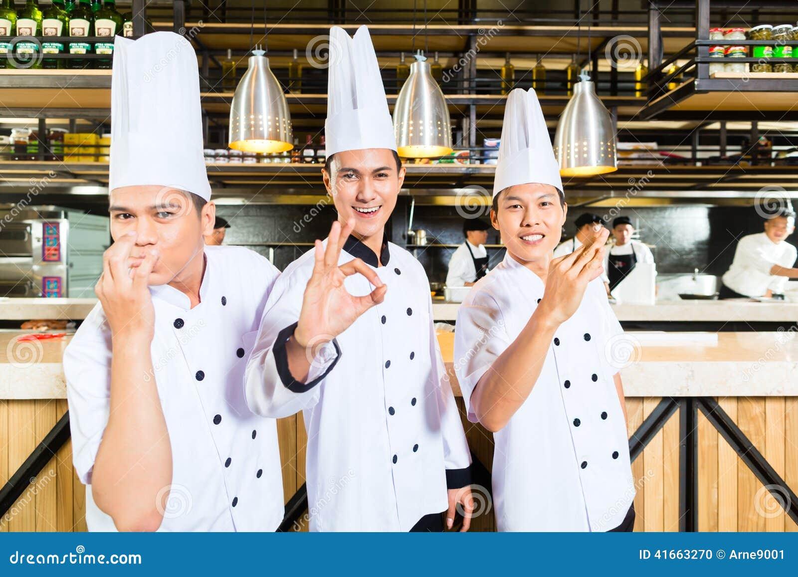 Азиатские шеф-повара варя в ресторане