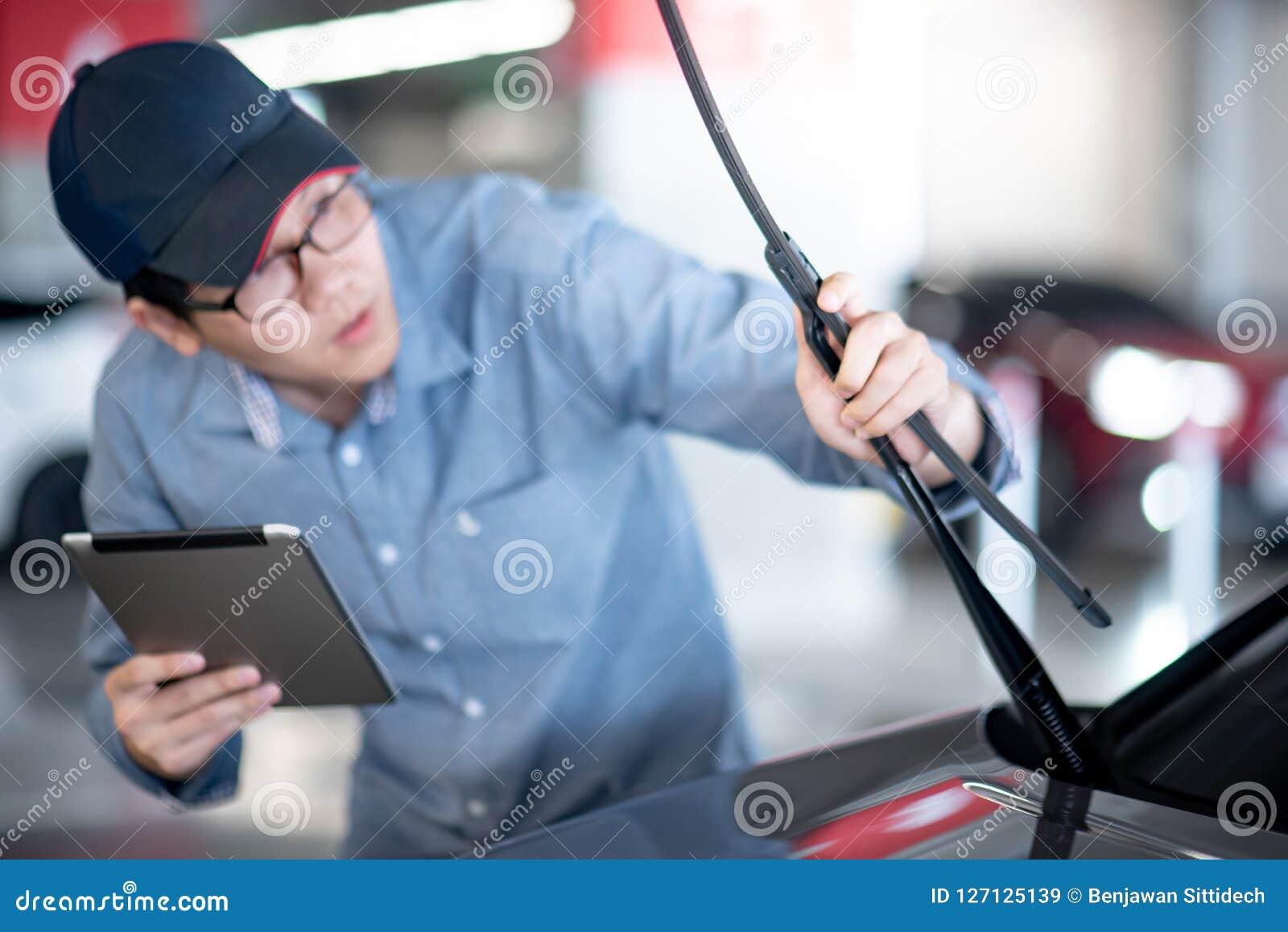 Азиатский автоматический механик проверяя счищатель лобового стекла