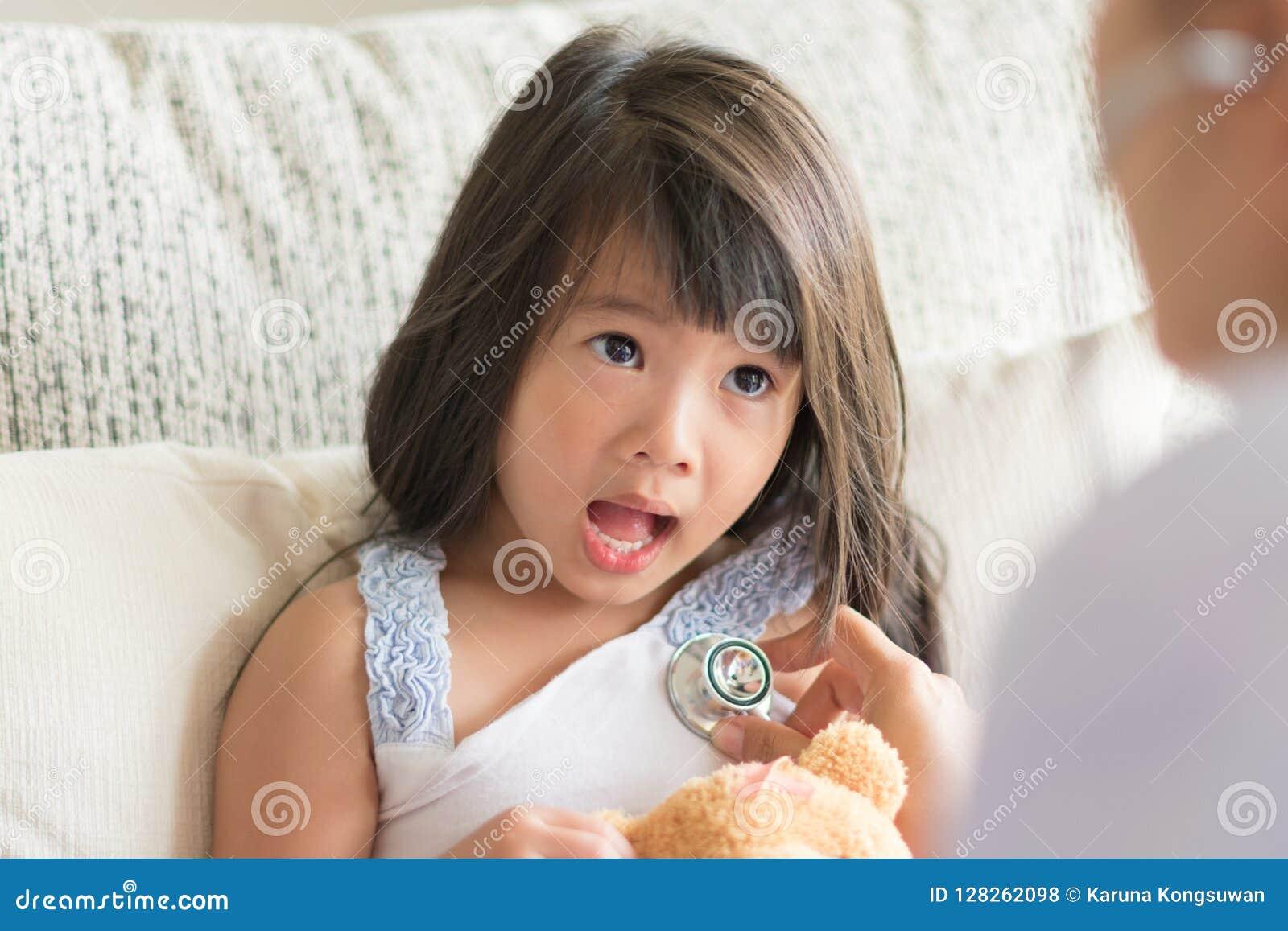 Азиатский взгляд маленькой девочки вспугнутый когда доктор рассматривая путем использование