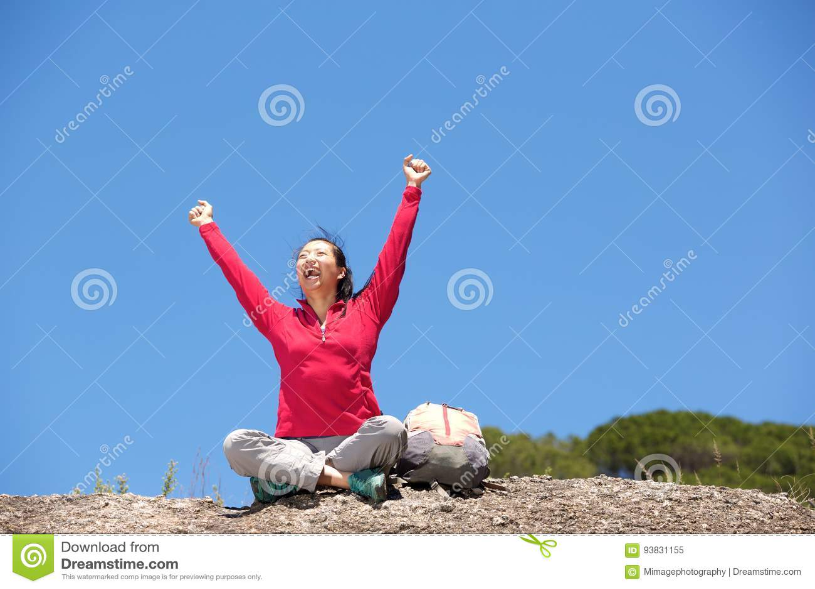 Азиатский женский hiker сидя outdoors при поднятые руки