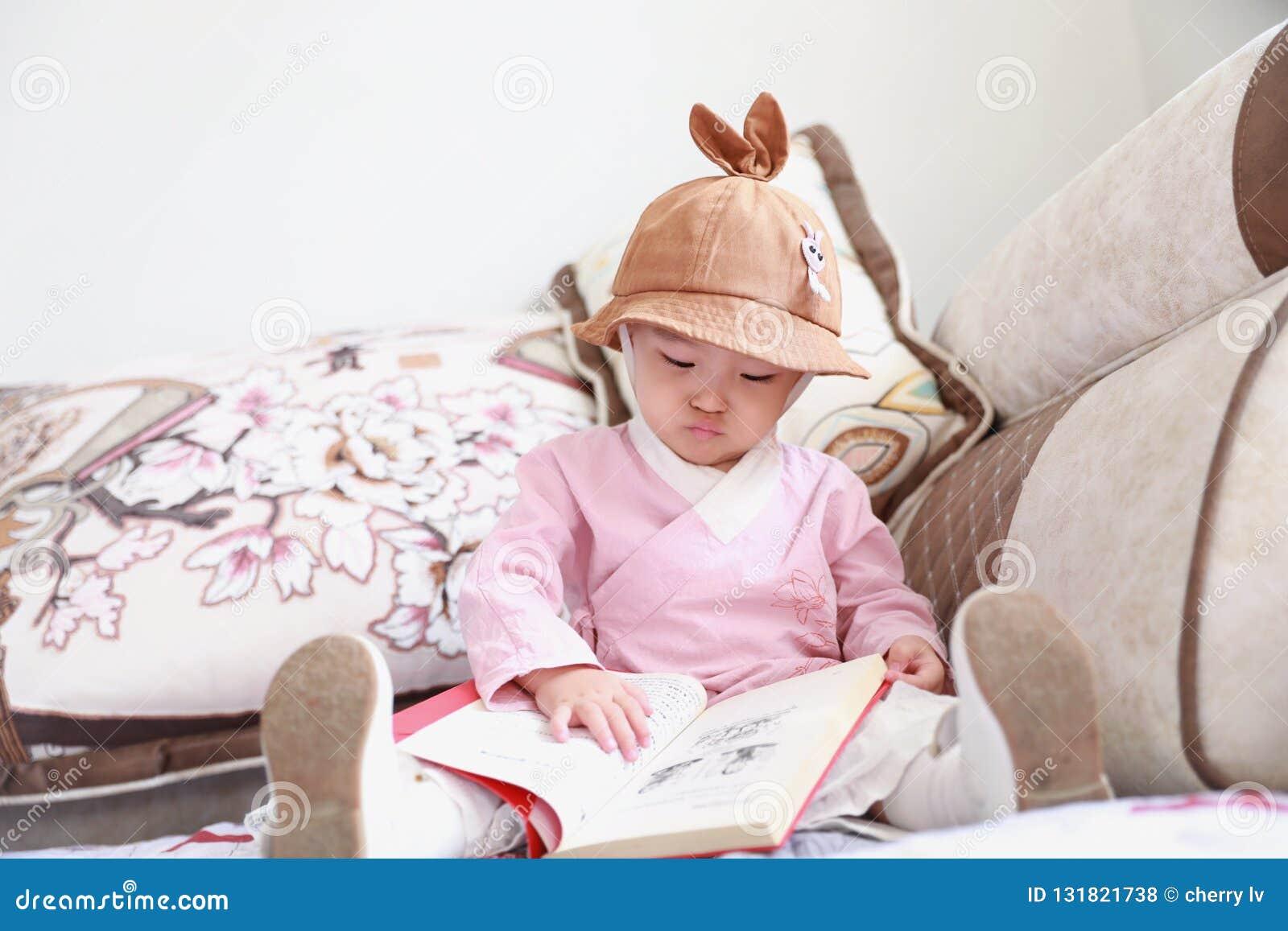 Азиатский китайский ребенок с книгой чтения шляпы на софе