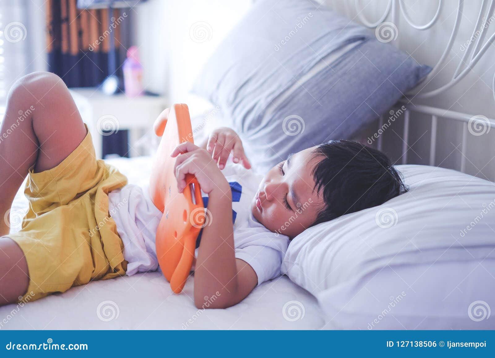Азиатский мальчик наблюдая онлайн видео на кровати