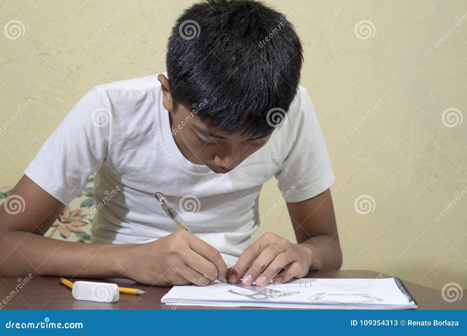 Азиатский мальчик уча и практикуя нарисовать формы 3D на тетради чертежа
