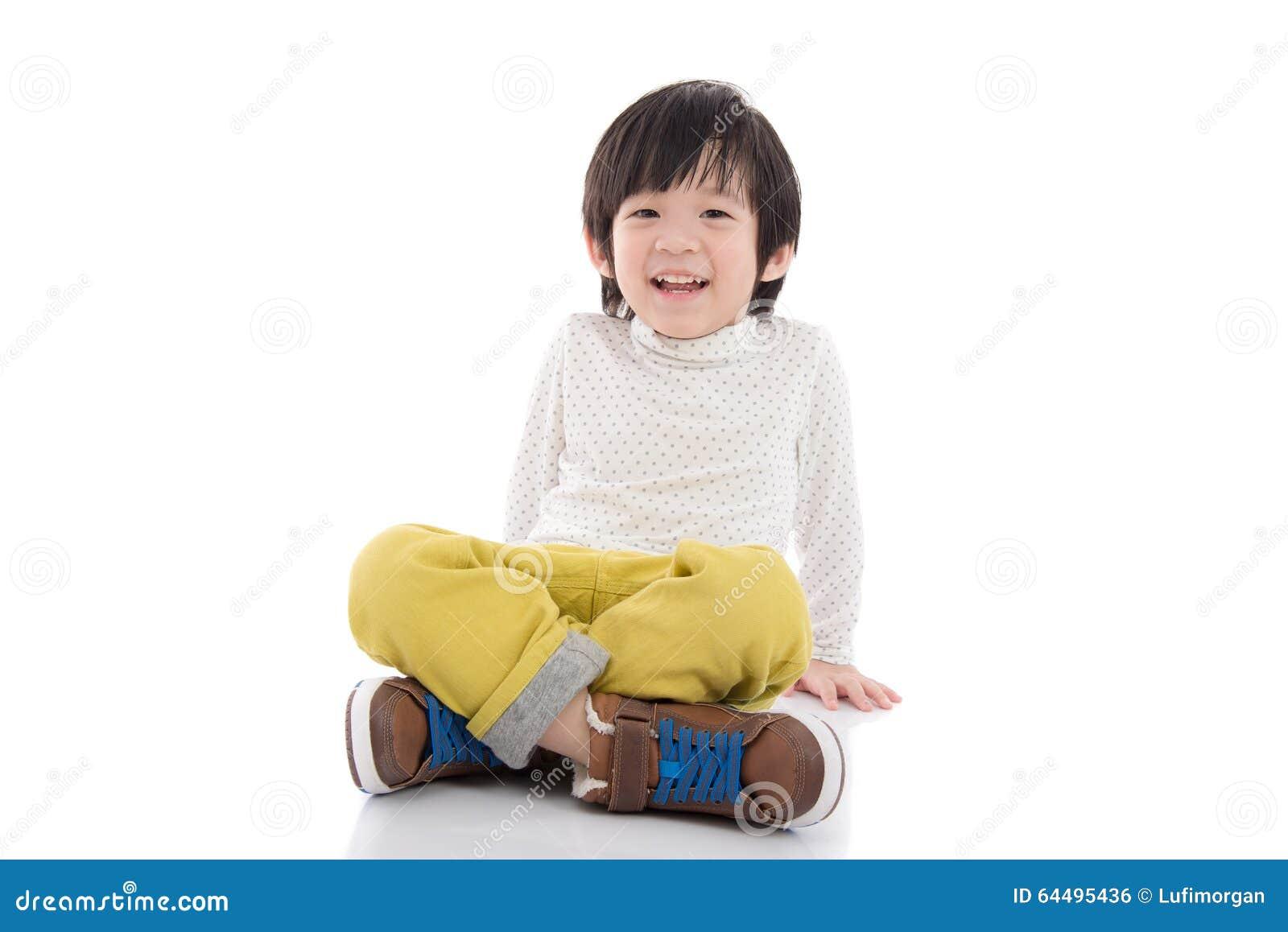 Азиатский мальчик сидя на белой изолированной предпосылке