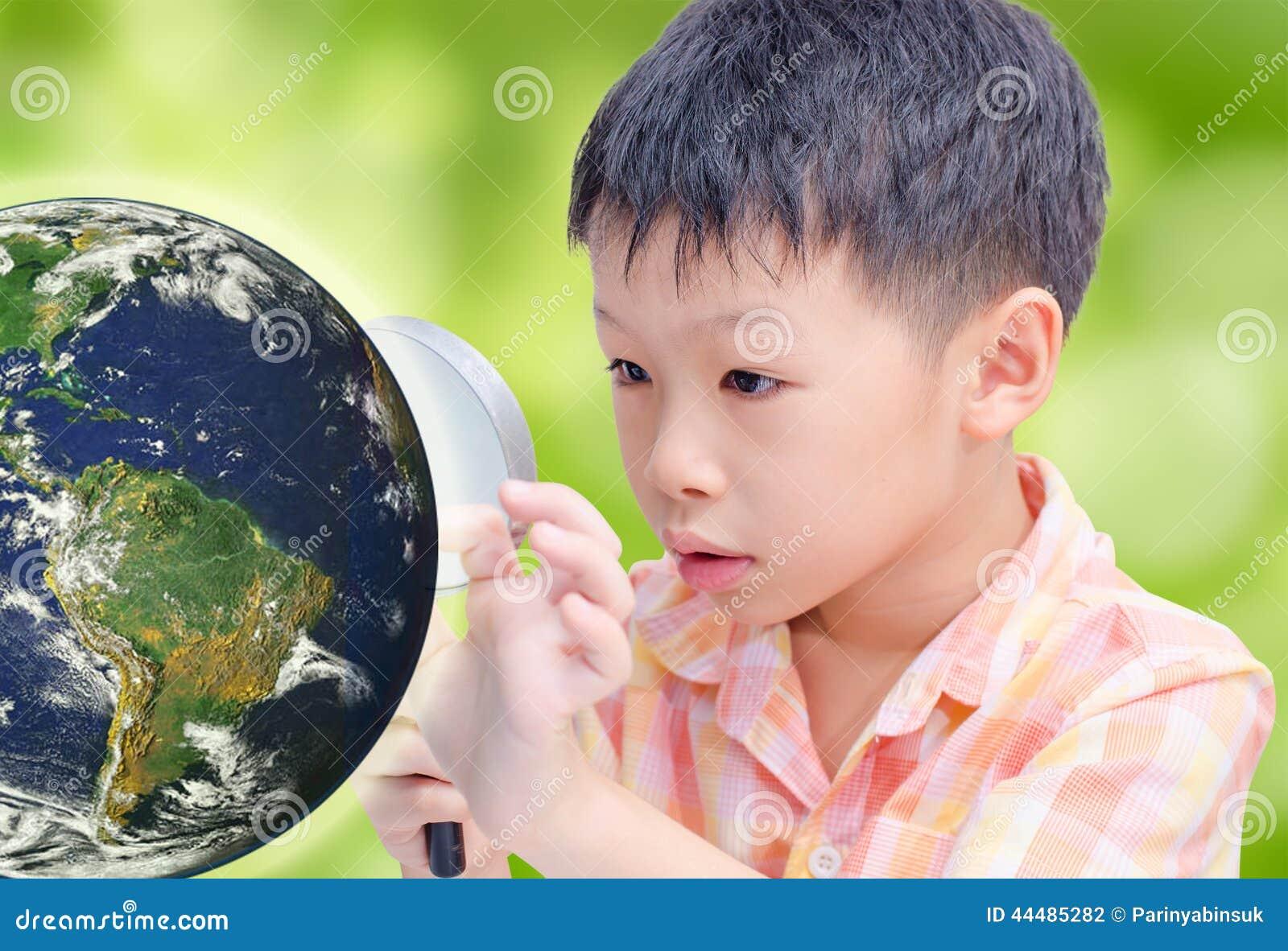 Азиатский мальчик смотря накаляя глобус лупой