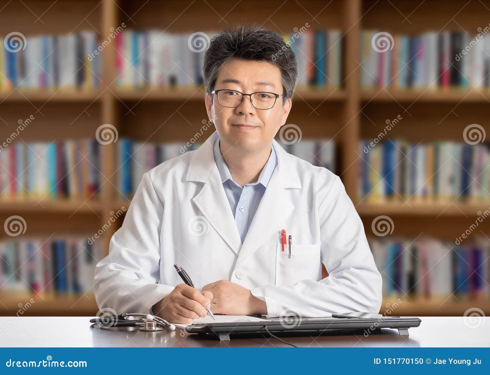 Азиатский мужской доктор сидя на усмехаться стола
