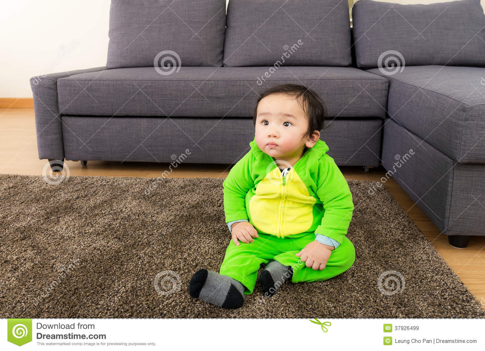 Азиатский младенец с костюмом партии хеллоуина динозавра