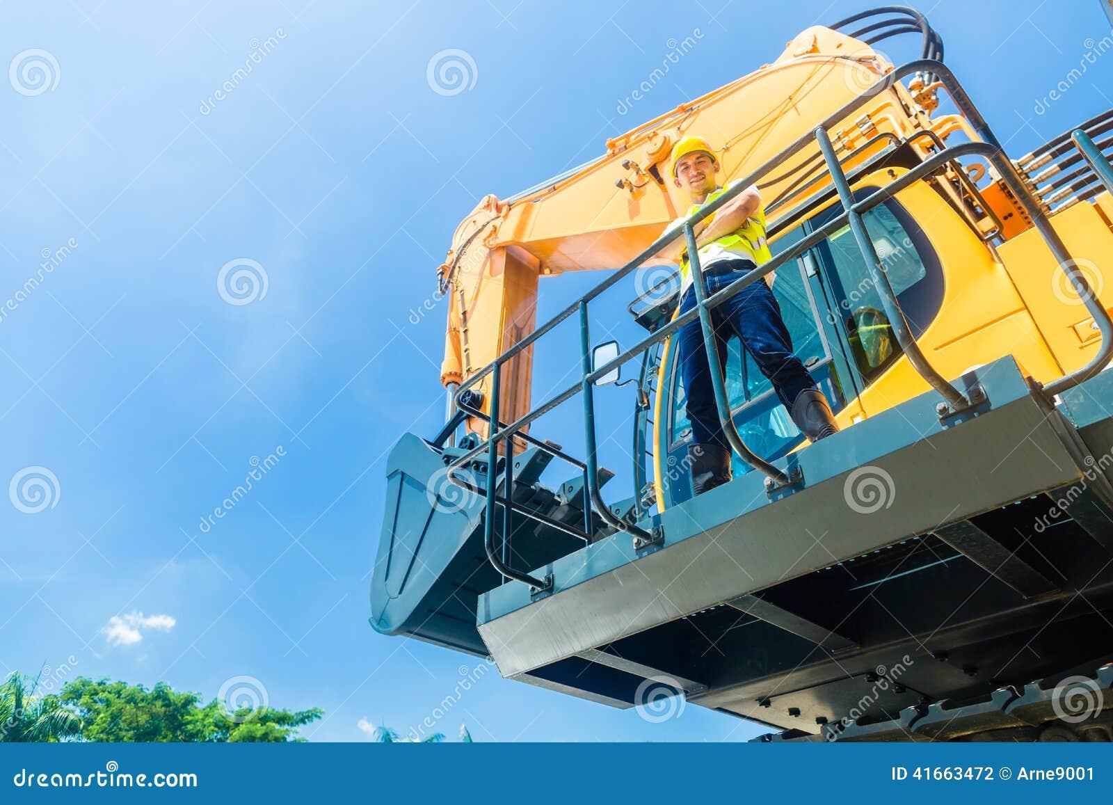 Азиатский рабочий-строитель на экскаваторе лопаткоулавливателя