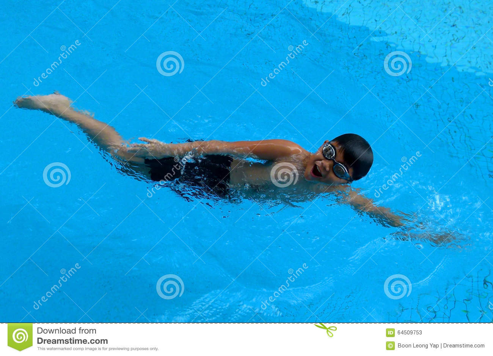 Азиатский ребенк плавает в бассейне - стиле переднего ползания