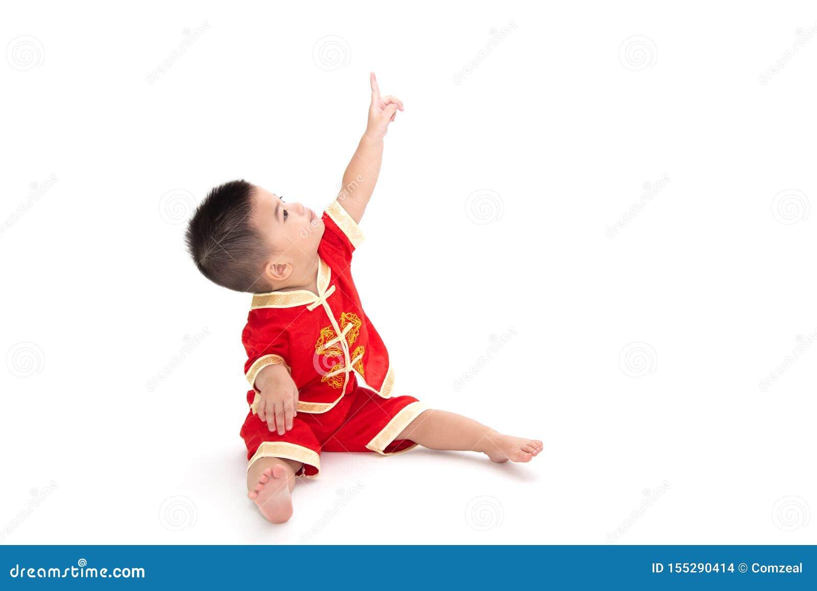 Азиатский ребенок сидит и указывающ на верхний и нося изолированный костюм традиционного китайского на белой предпосылке,